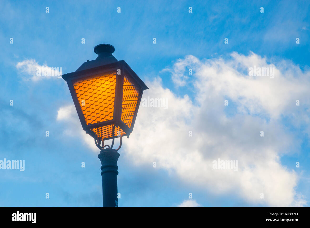 Lit up street light against blue sky. Stock Photo