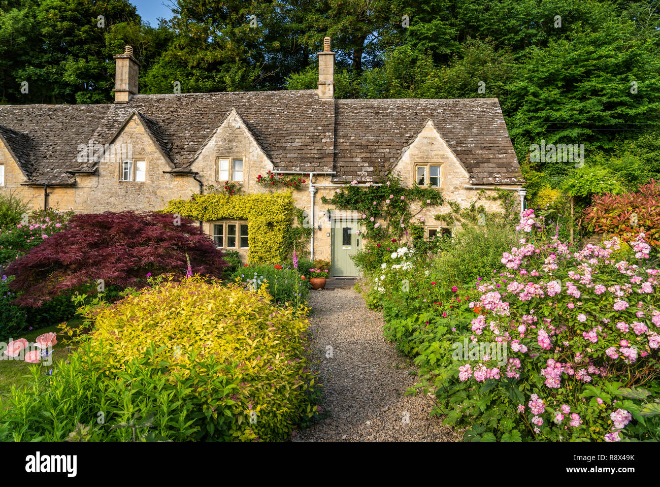 A Large Stone Home With Flower Gardens In The Cotswold Village Of