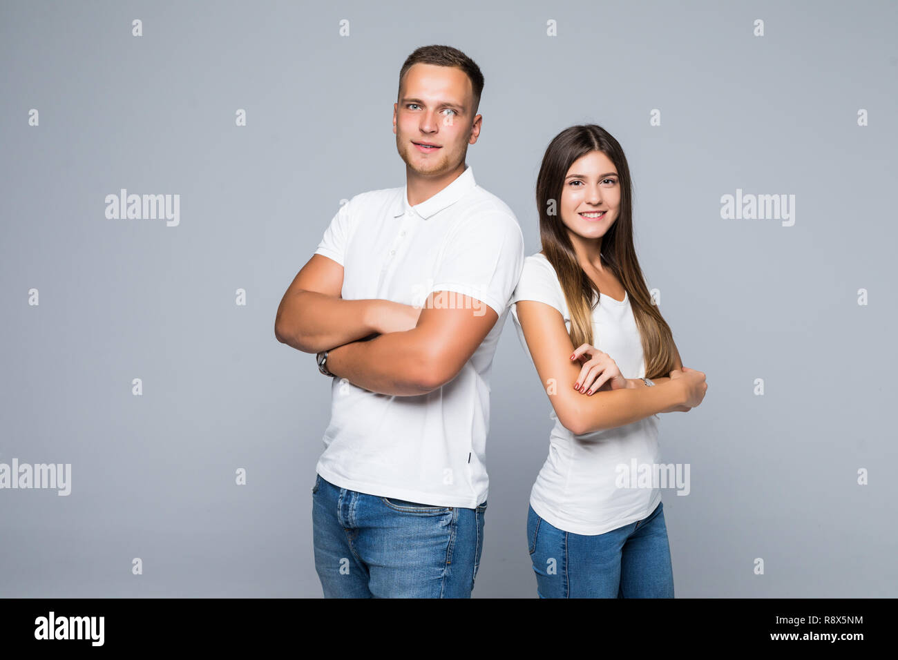 Portrait of an couple standing back to back and looking at camera over gray wall - Stock Image