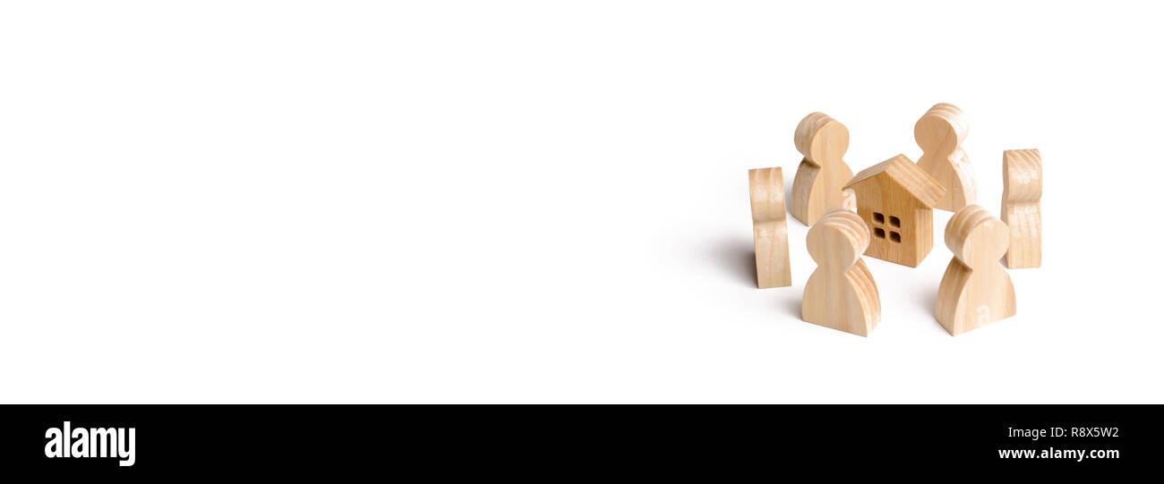 Wooden figurines of people stand around the house. Search for a new home and real estate. Buying or selling a home. Moving to a new home. Rent or cons - Stock Image