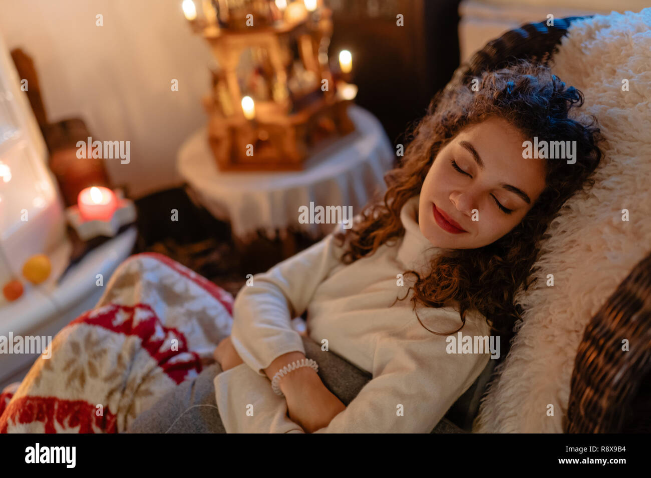 Beautiful young woman with curly hair is taking a nap with Christmas lights in the background - Stock Image