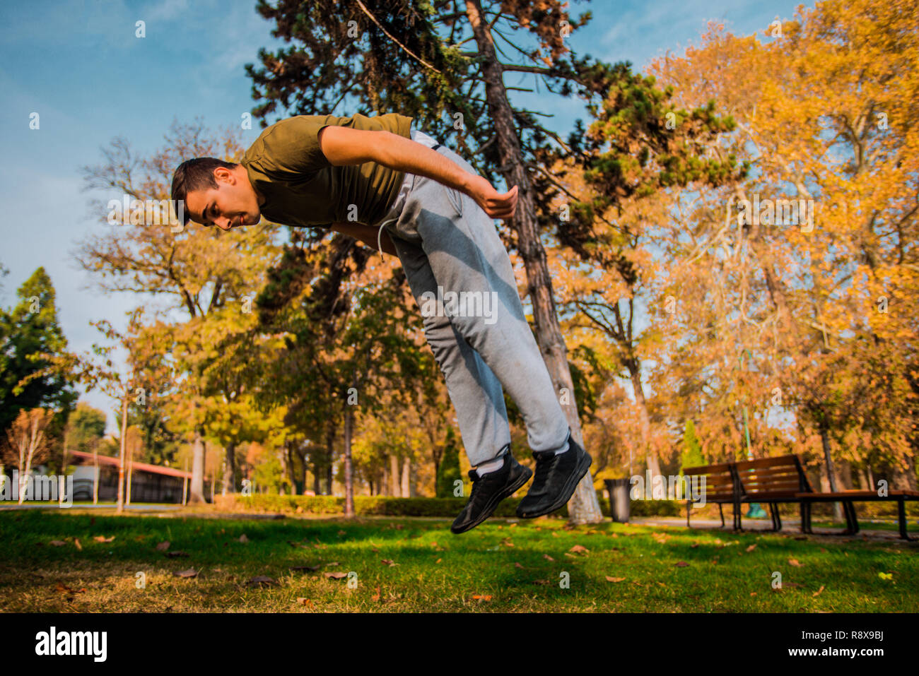 Young traceur doing frontflip jumping in nature - Stock Image