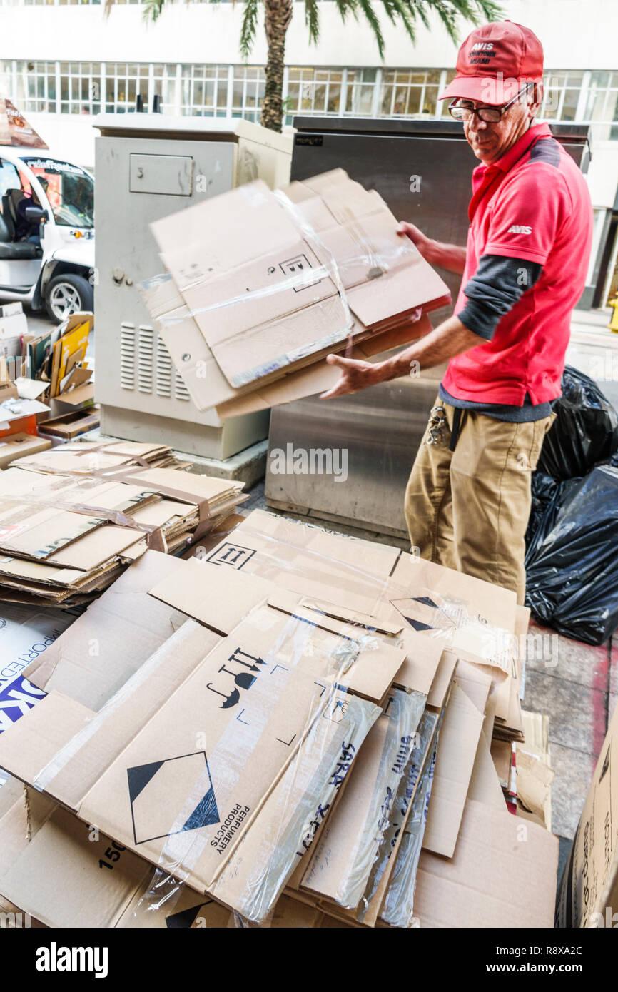Miami Florida downtown Hispanic man breaking down cardboard boxes taking apart recycling - Stock Image