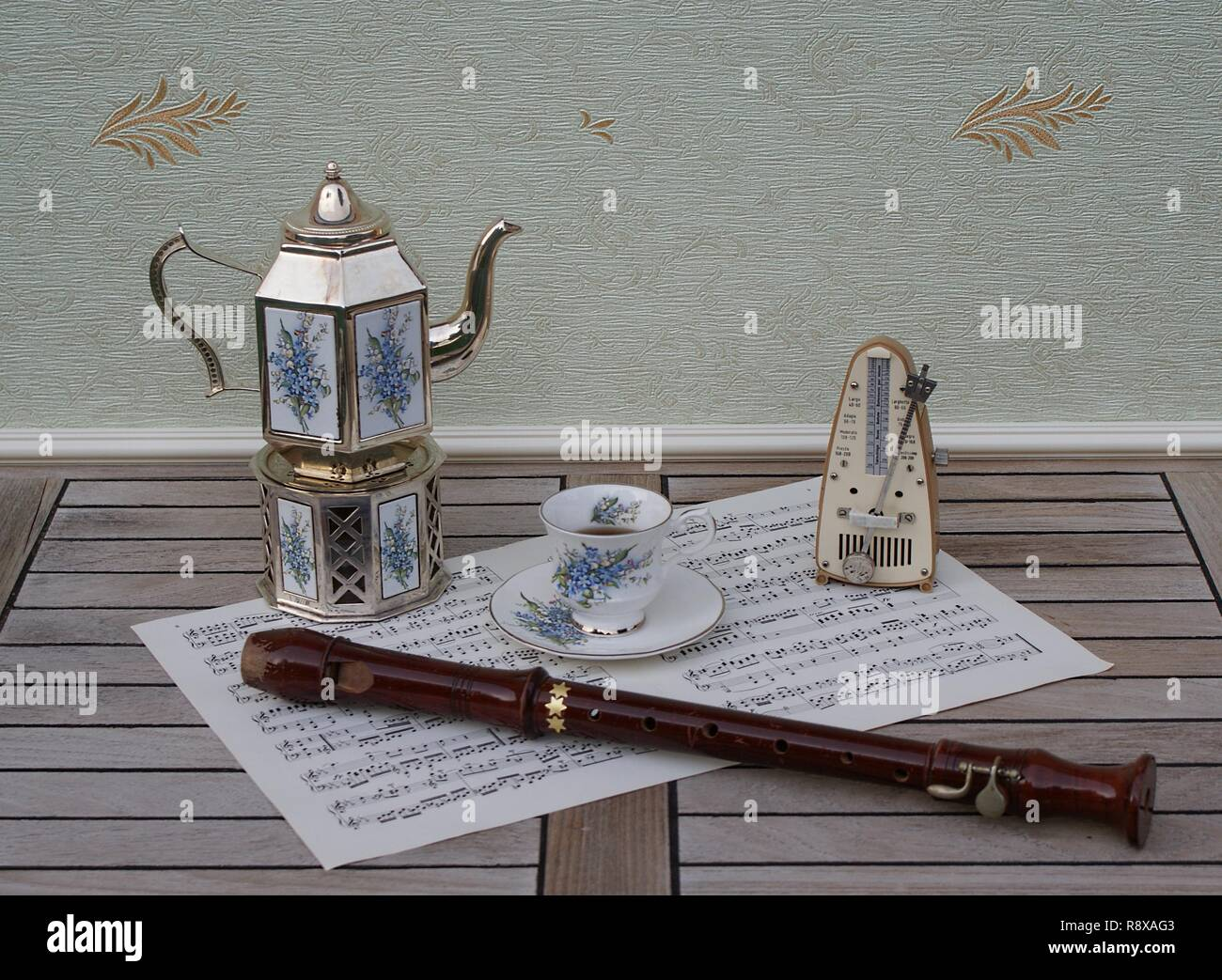 English teacup and saucer, silver-plated teapot on a silver stove, with floral decor, metronome for music and a block flute on a sheet of music - Stock Image