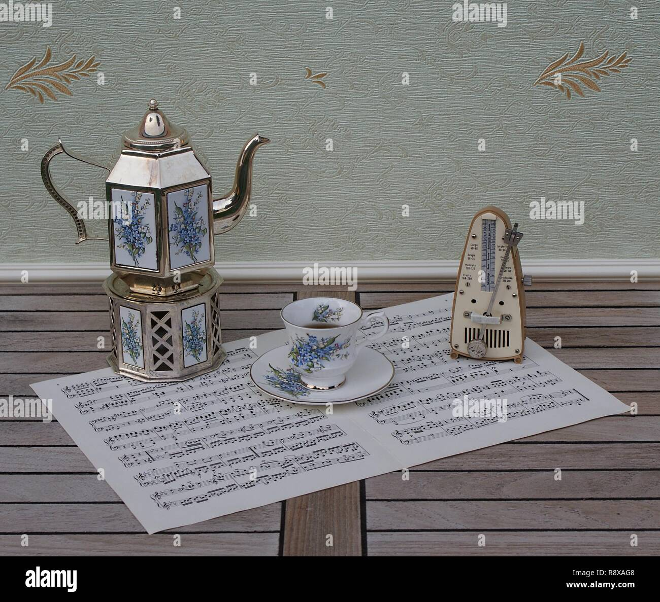 English teacup and saucer, silver-plated teapot on a silver stove, with floral decor and metronome for music on a sheet of music - Stock Image