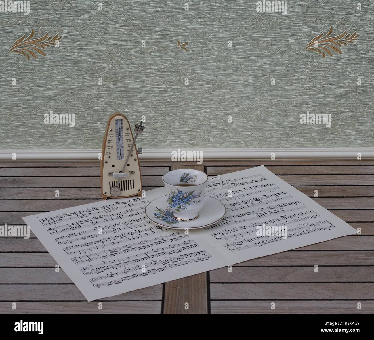 English teacup and saucer with floral decor and silver rim, and a metronome for music on a sheet of music - Stock Image