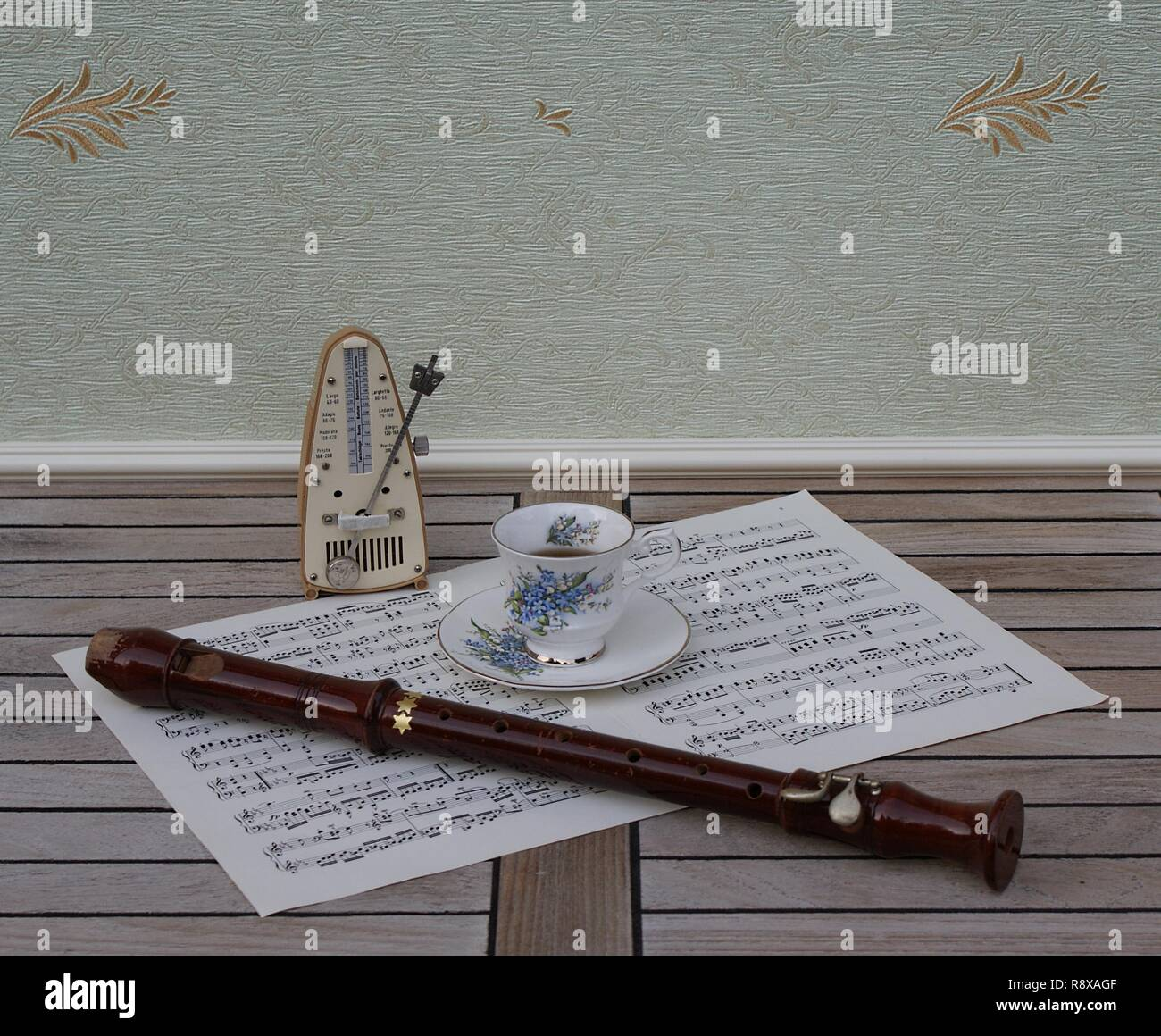 English teacup and saucer with floral decor and silver rim, metronome for music and a block flute on a sheet of music - Stock Image
