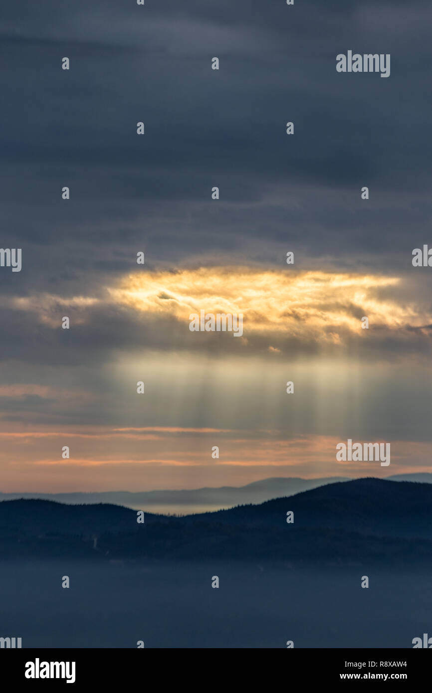 Sunray shines through clouds over the mountains and a sea of fog - Stock Image