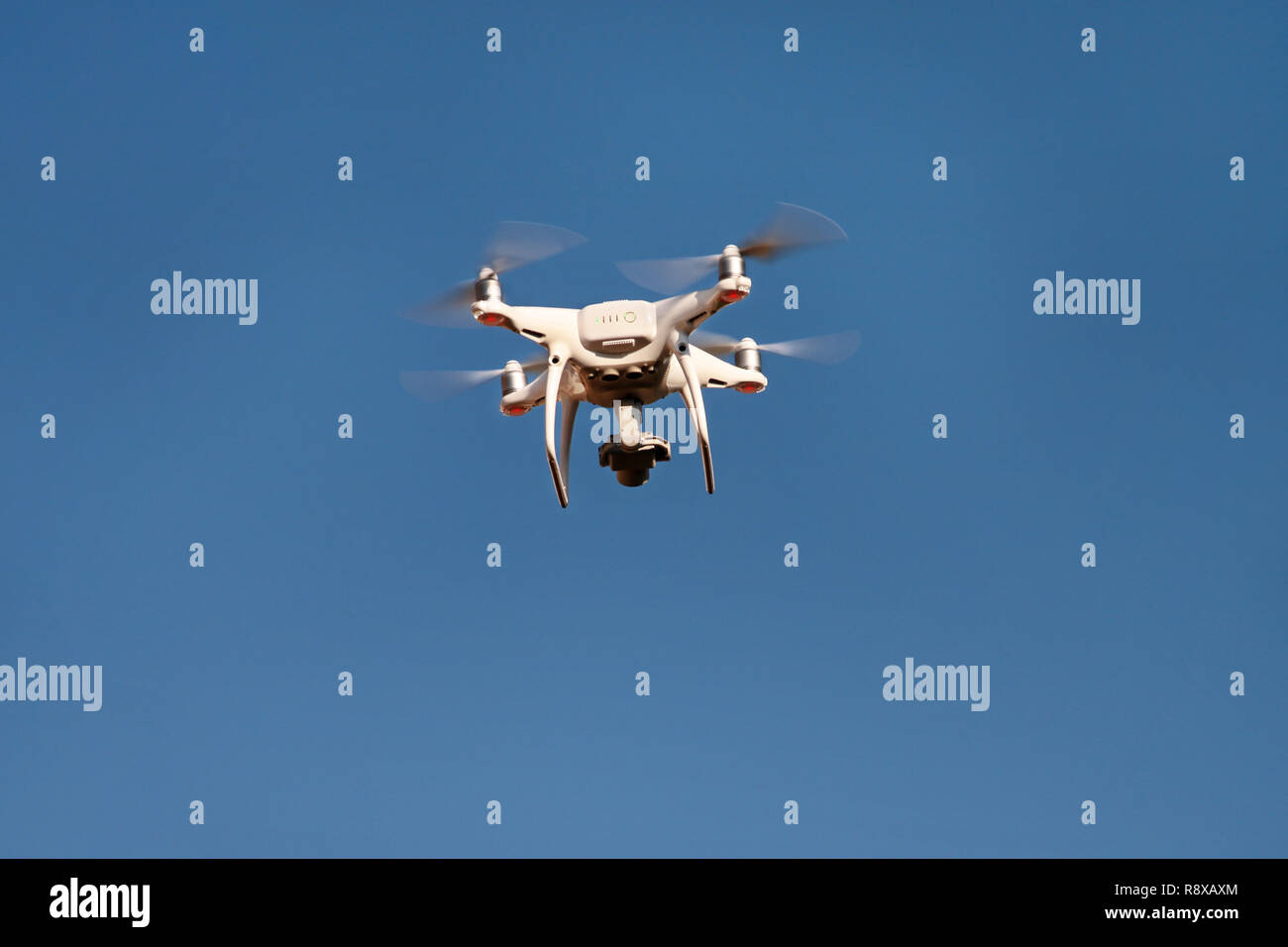 Drone quad copter fly on blue sky in background. Modern drone is flying in air, to take photos and record footage from above. Drone. - Stock Image