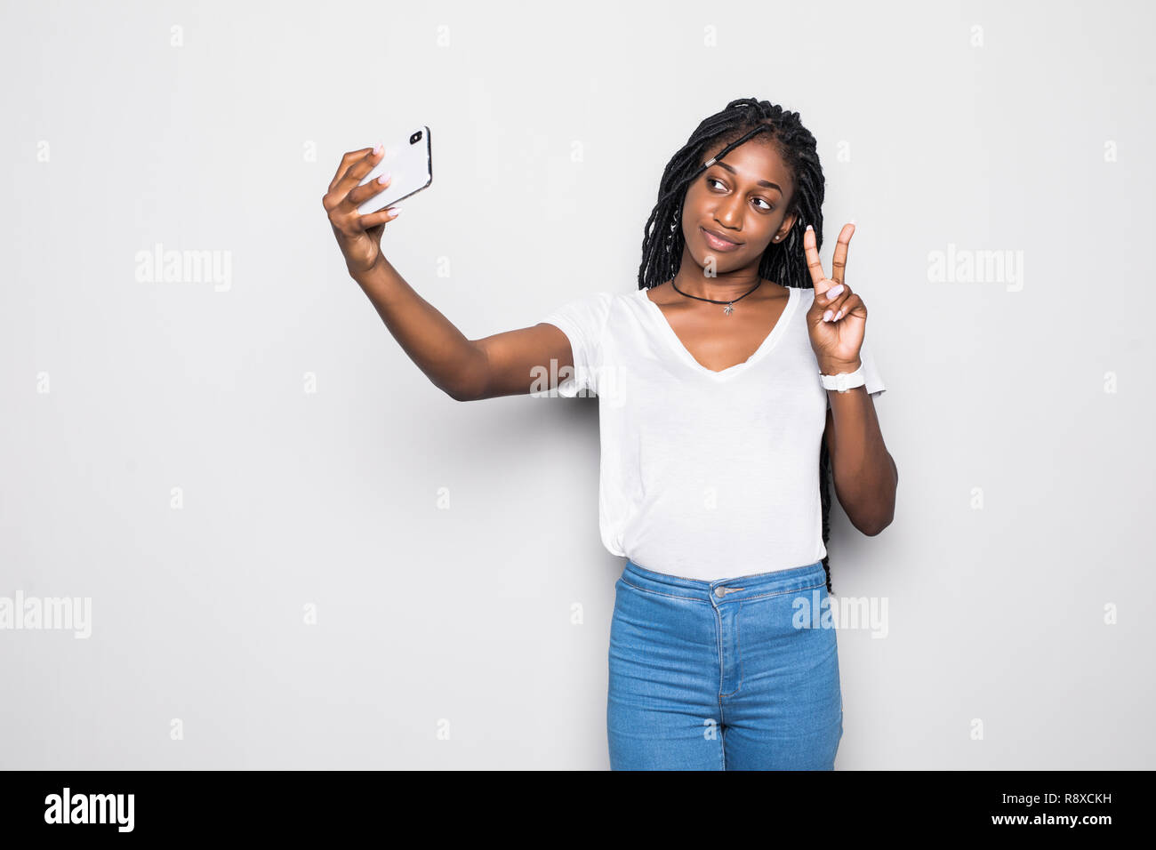 Young funny african casual lady grimacing and making selfie on smartphone isolated over gray - Stock Image
