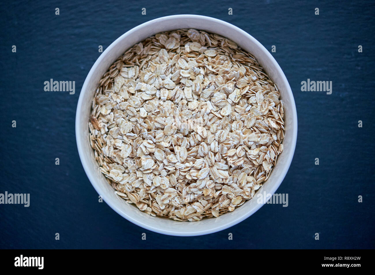 Dry rolled oatmeal in bowl isolated on dark background. Scattered oat flakes. Stock Photo