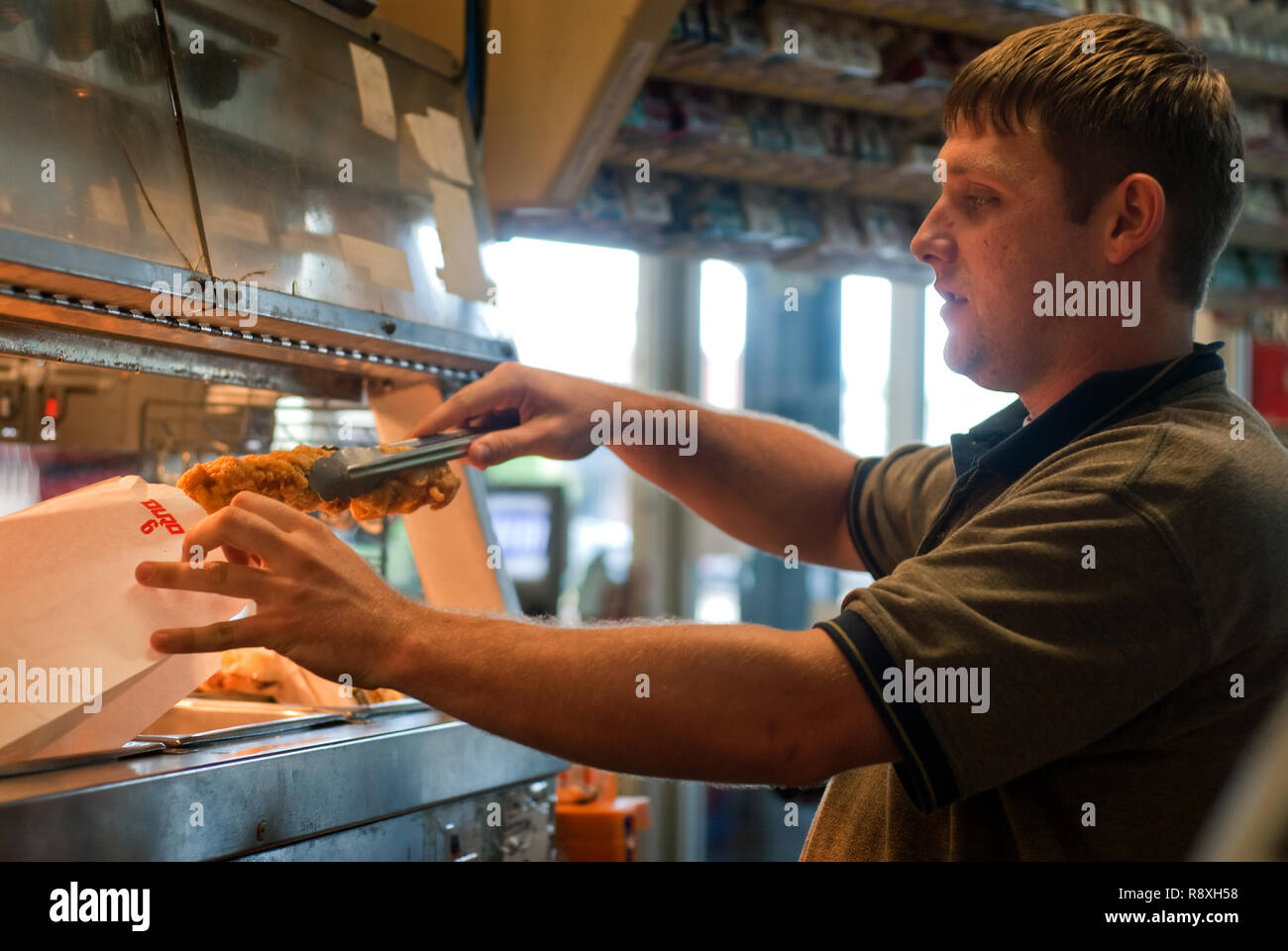 A gas station employee places fried chicken strips in a bag, July 17, 2011, in Oxford, Mississippi. - Stock Image