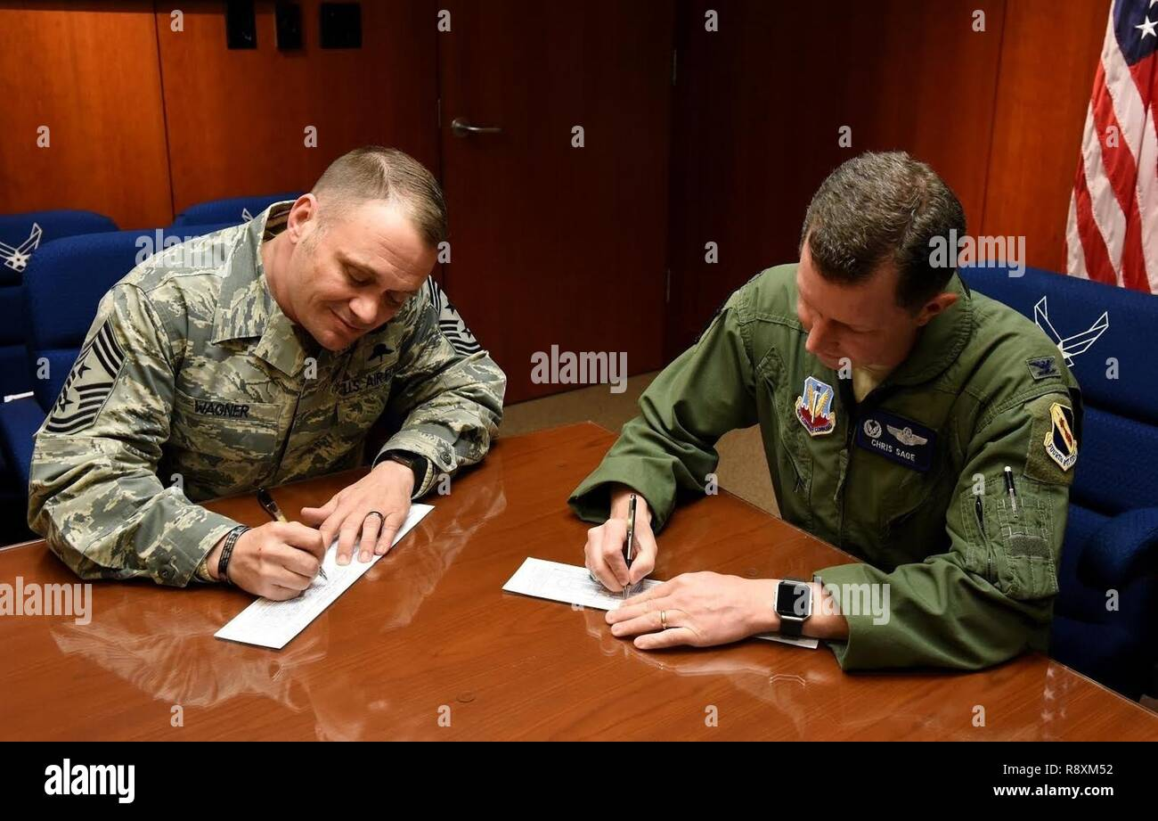 Chief Master Sgt. Shane Wagner, 4th Fighter Wing command chief, and Col. Christopher Sage, 4th FW commander, sign their donation forms for the 2017 Air Force Assistant Fund. The AFAF is an Air Force-wide campaign that generates donations for four different charities: Air Force Villages, Air Force Enlisted Villages, The General and Mrs. Curtis E. Lemay Foundation and the Air Force Aid Society. - Stock Image