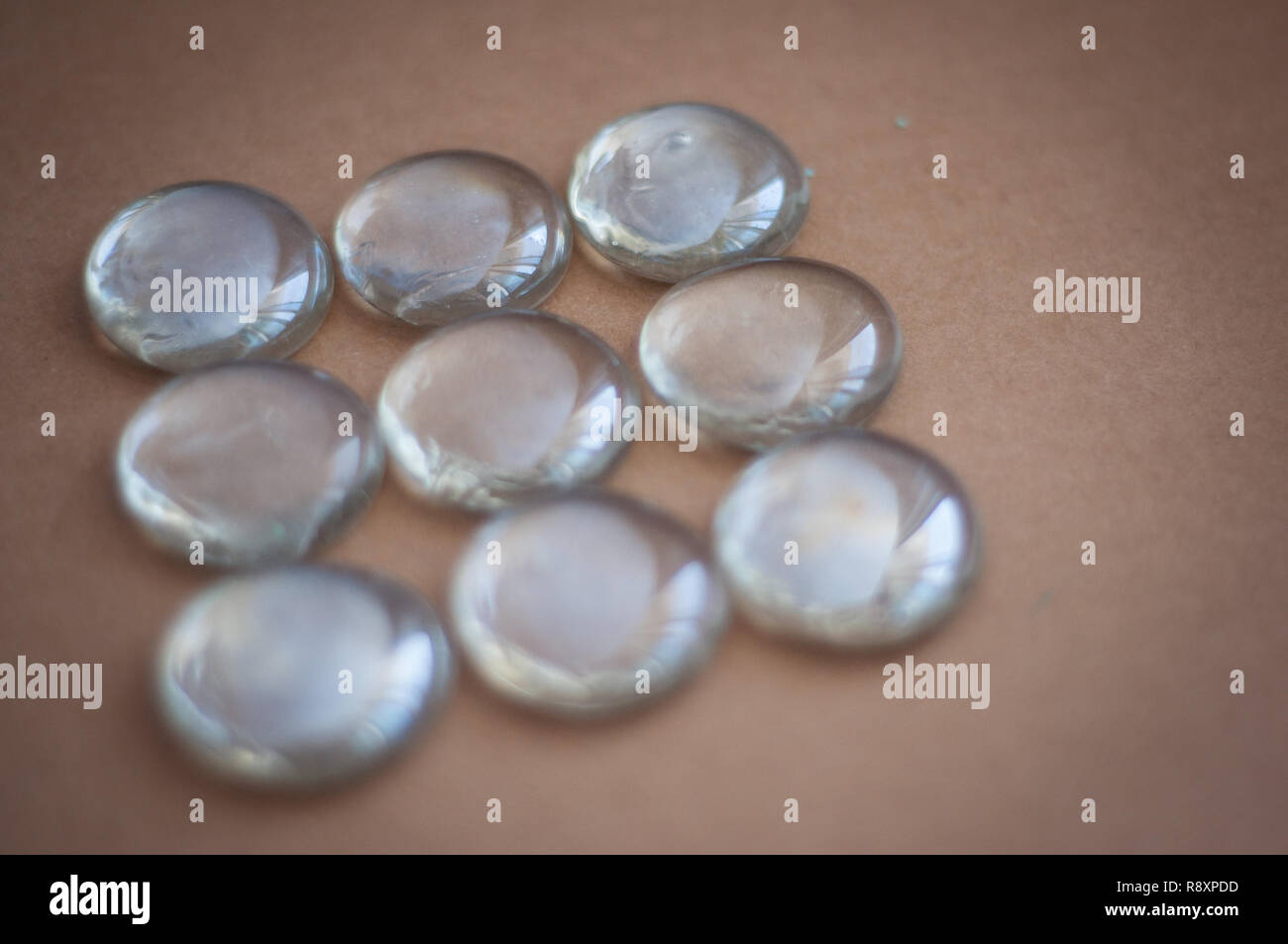 Clear marbles with light reflections on a brown background. - Stock Image