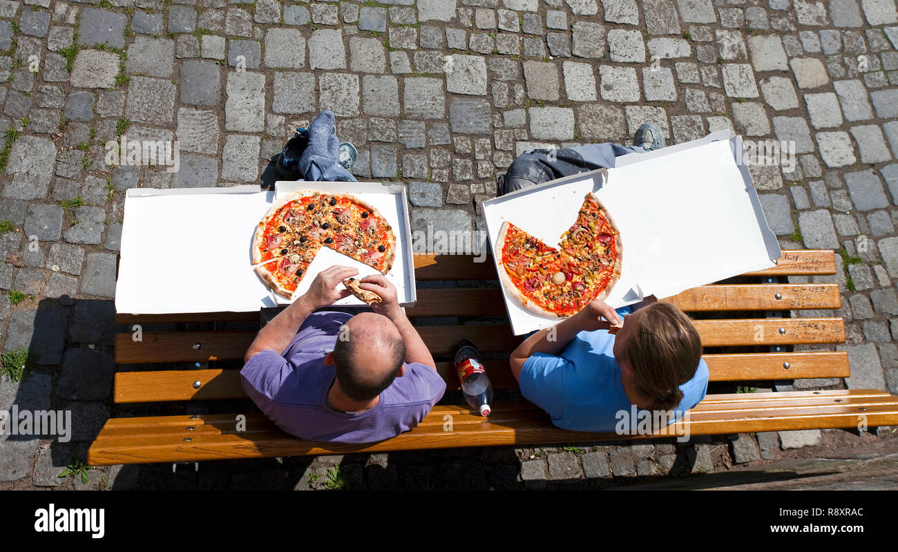 Worker sitting on a bench and eating a Pizza, old town, Nuremberg, Franconia, Bavaria, Germany, Europe Stock Photo