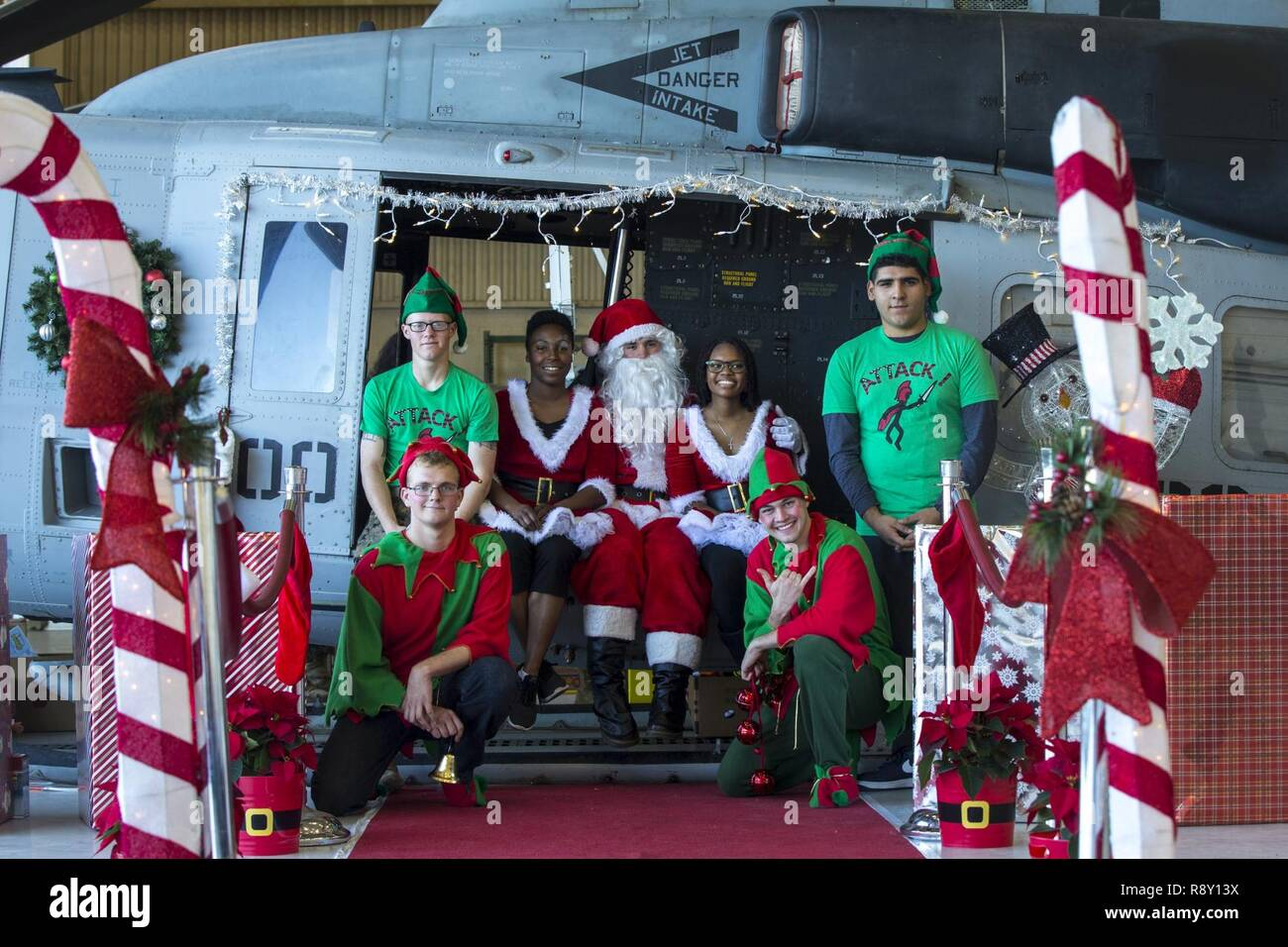 Santa Claus and his helpers take a group photo during the