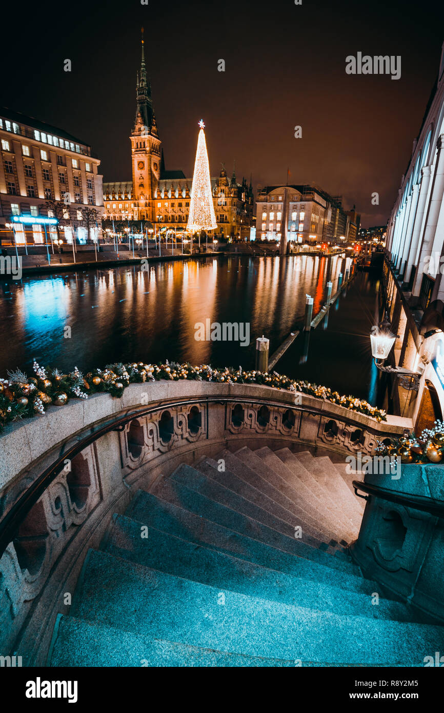 Christmas market on the Town hall square. Decorated alsterfleet stairs and beautiful Illuminated x-mas trees in front of city hall in Hamburg at night - Stock Image