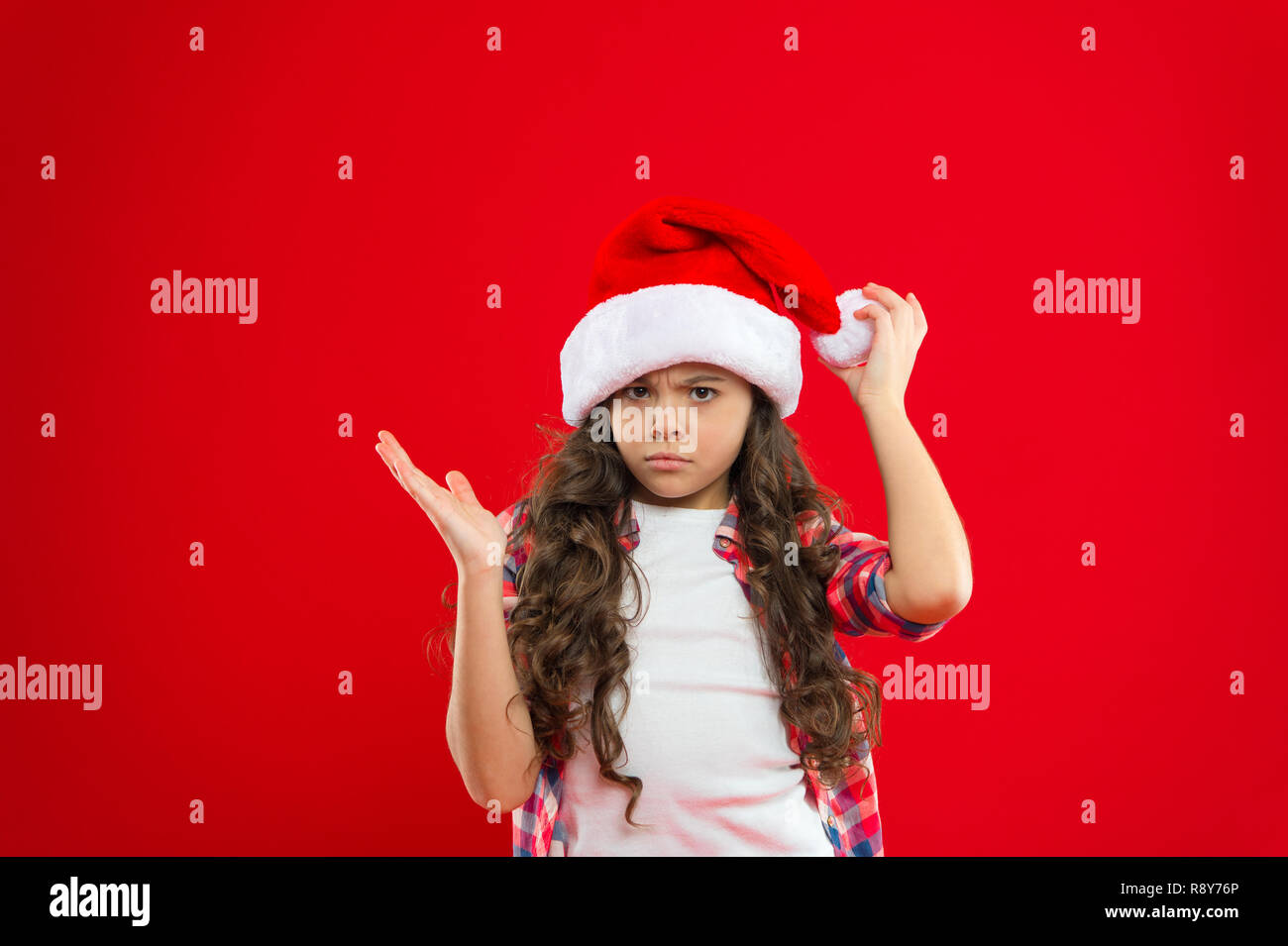 50632ec6aeab0 Little girl child in santa red hat. Christmas shopping. Present for Xmas.  Childhood. New year party. Santa claus kid. Happy winter holidays. Small  sad girl.