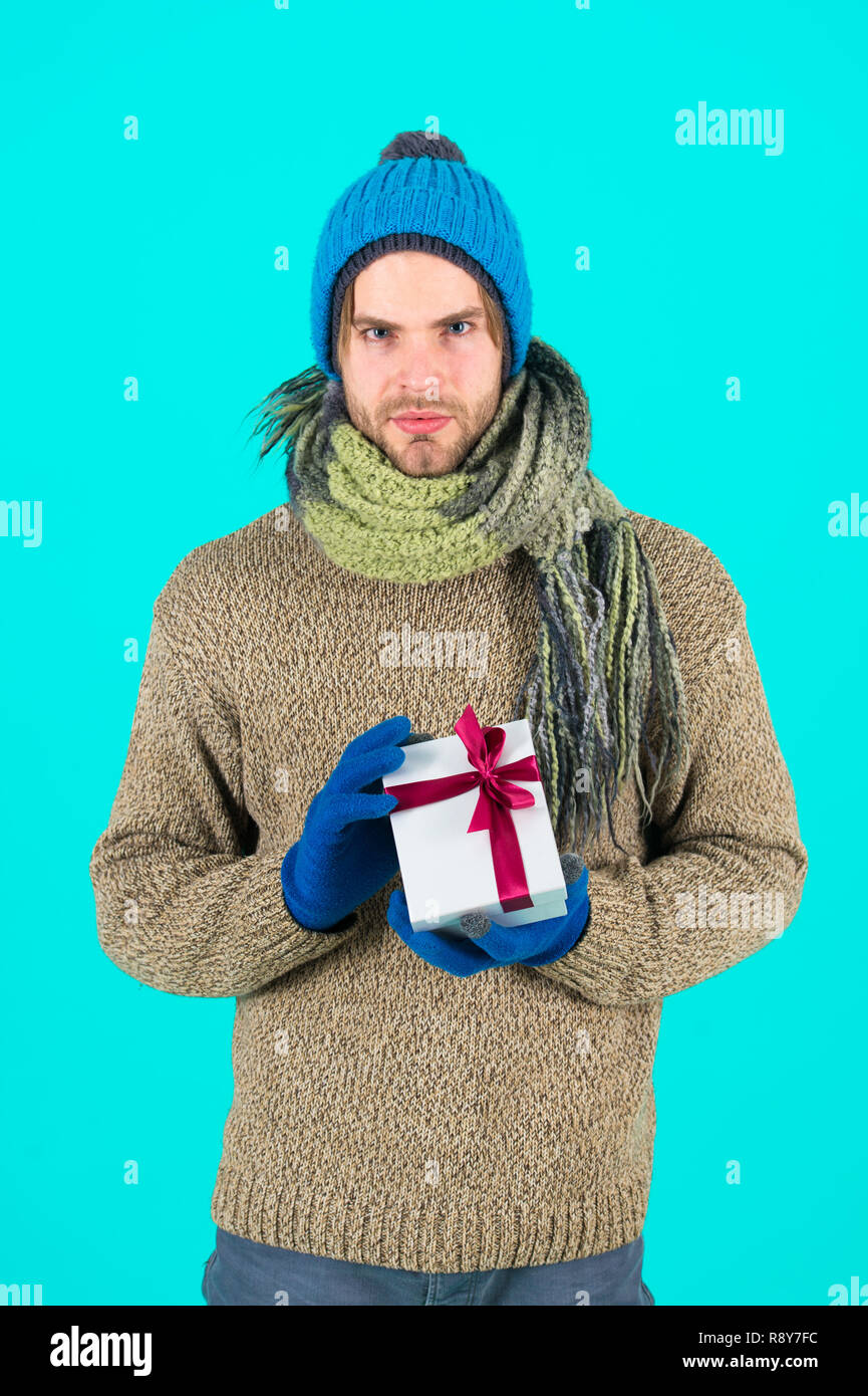 My congratulations. Man bearded handsome wear winter hat scarf gloves hold gift box. Hipster hold christmas gift with bow. Holiday present concept. Winter holidays. Give gift spread happiness. - Stock Image