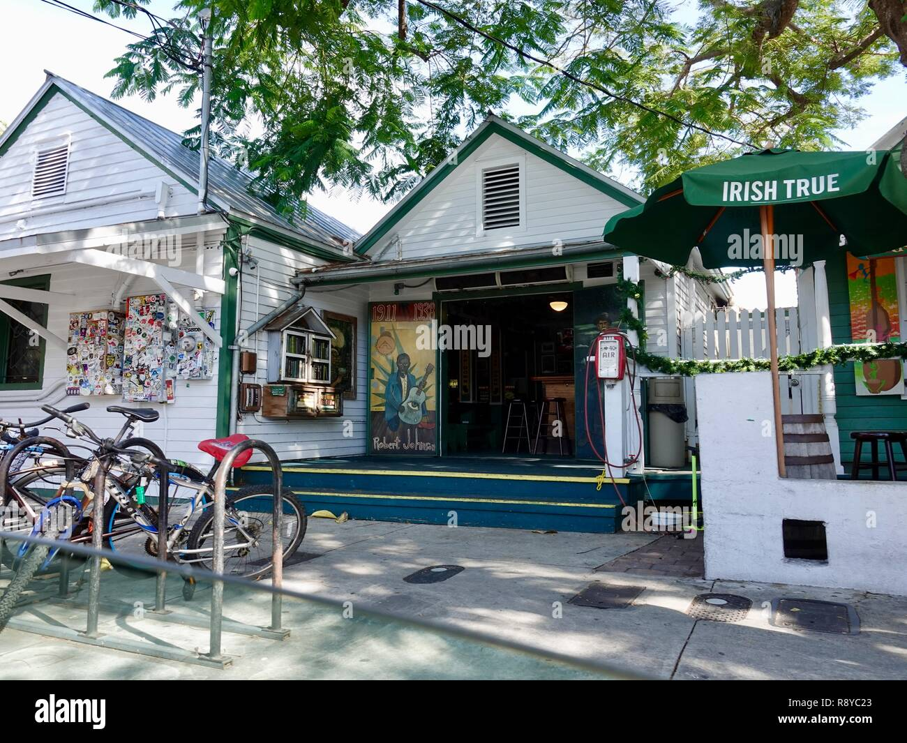 Shady sidewalk view of classic Key West, Florida buildings at Green Parrot Bar on Whitehead Street, with mural tribute to Robert Johnson. Stock Photo