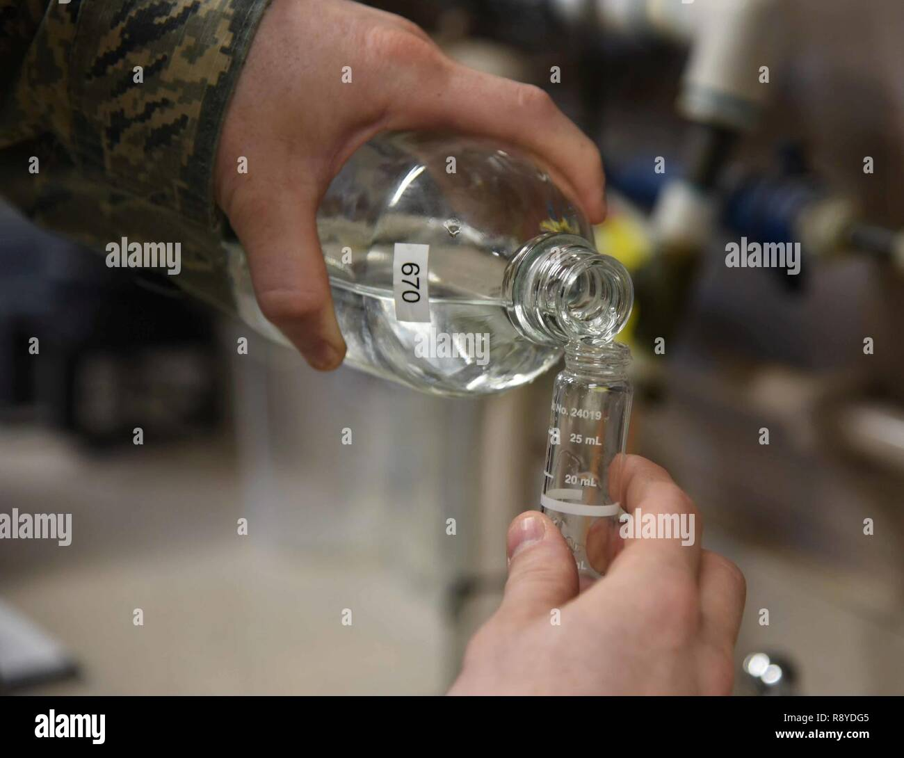 Staff Sgt. Shane Pentheny, 22nd Civil Engineer Squadron Water and Fuels System Maintenance technician, pours water into a small vial in order to test the chlorine, fluoride and pH levels March 9, 2017, at McConnell Air Force Base, Kan. If the samplings yield low readings, which sometimes happens in low-use buildings, the normal procedure is to flush the building until desired results are achieved. - Stock Image