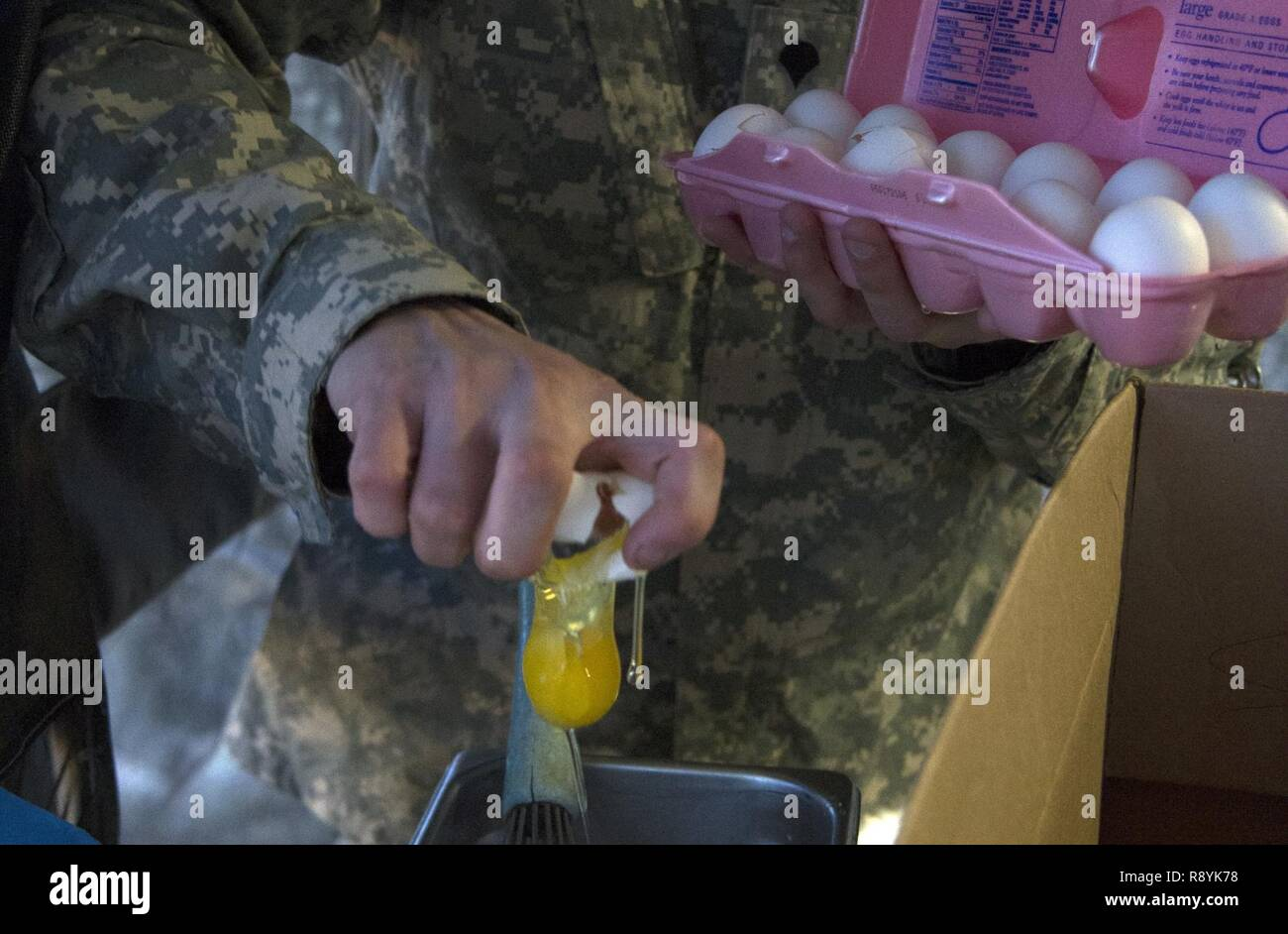 A U.S. Army Reserve Soldier from the culinary team of the 391st Military Police Battalion, breaks eggs in order to prepare crepes during food service operations in the field as part of the 49th Philip A. Connelly Award for Excellence in Army Food Service competition at Camp Blanding, Florida, March 17, 2017. The 391st MP Bn., one of four Army-wide finalists, selected Camp Blanding, Florida, as their location for the final level of testing in the competition. - Stock Image