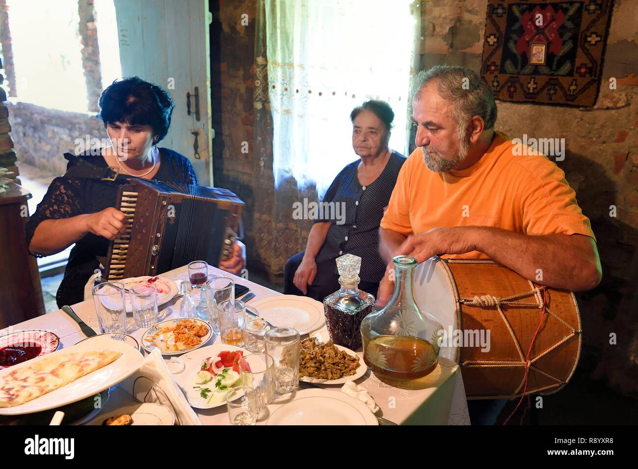 Georgia, Kakheti, Akhmeta, traditional festive meal in a Tusheti family, songs accompanied by accordion and drum - Stock Image