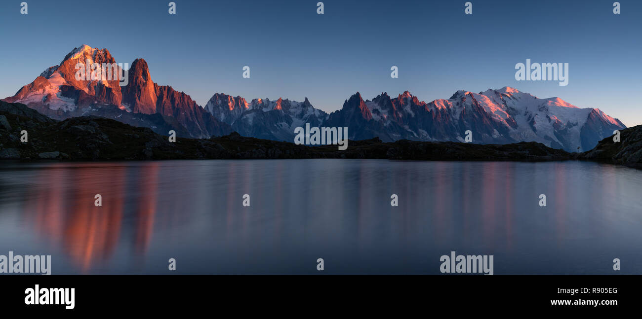 Panorama of the Alps near Chamonix, with Aiguille Verte, Auguille du Midi and Mont Blanc, during sunset at Lac des Cheserys. - Stock Image