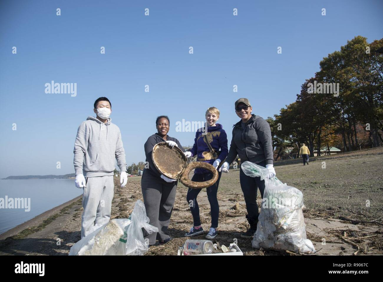 Team Misawa personnel hold their trash collection after a cleanup in Misawa City, Japan, Oct. 28, 2017. The group of volunteers picked up approximately 100 pounds of trash, collecting everything from small plastic bottles to a large toilet seat. As an effective community outreach event, Misawa Air Base often holds site cleanups to reinforce the strong foundation of trust between the U.S. and its host nation of  Japan. - Stock Image