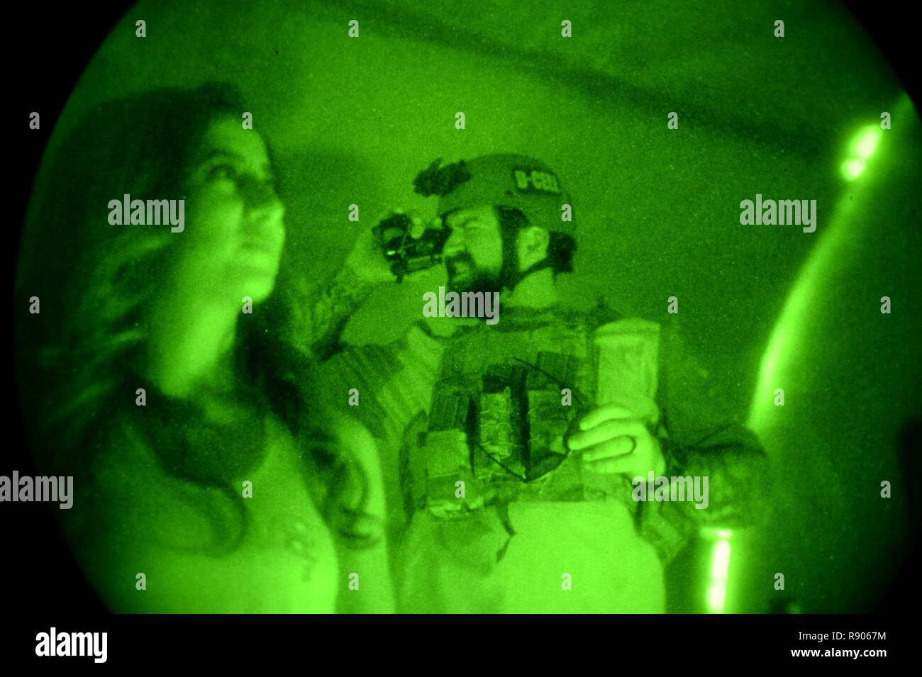 Tampa Bay Buccaneers cheerleader Tessa and offensive guard Evan Smith try out PVS-14 night-vision goggles with U.S. Special Operations Command Deployment Cell personnel during a visit to MacDill Air Force Base in Tampa, Fla., Nov. 7, 2017. The football players and cheerleaders toured USSOCOM and other base facilities to meet with currently serving personnel and to experience a glimpse of military life. Stock Photo