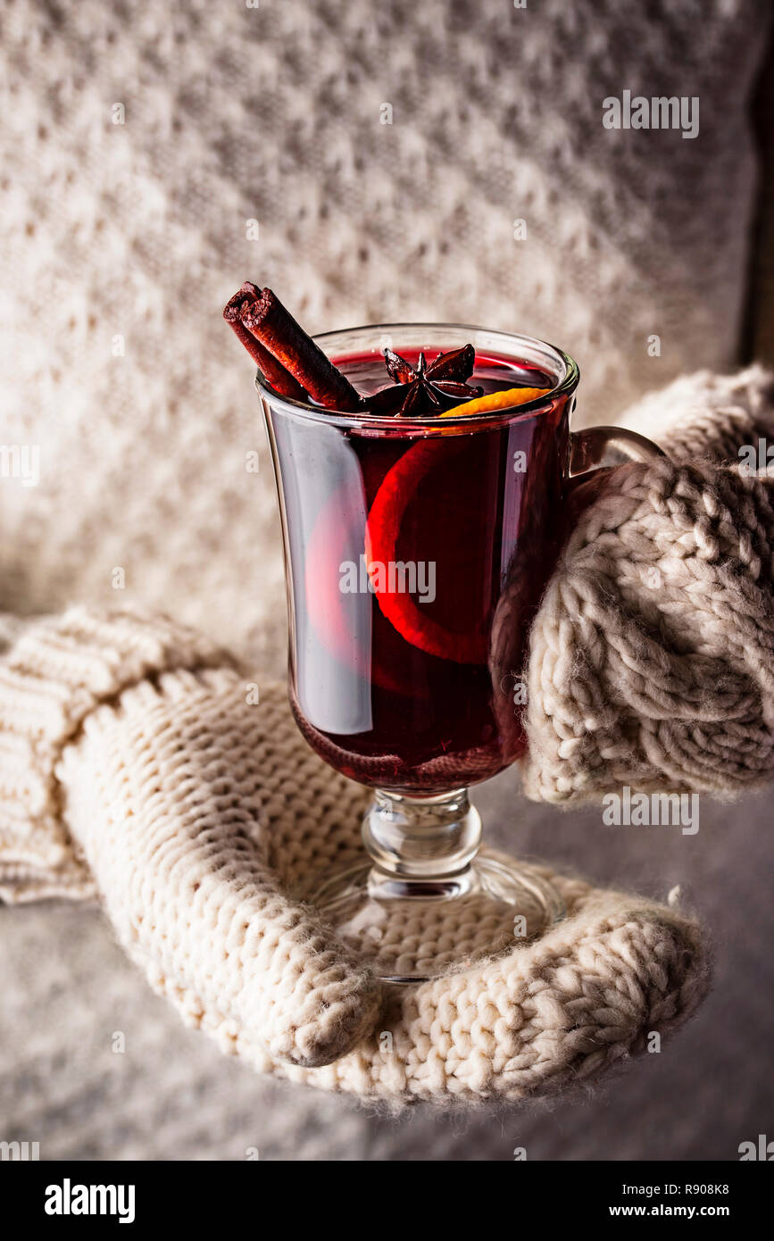 Girl in mittens hold glass of mulled wine - Stock Image