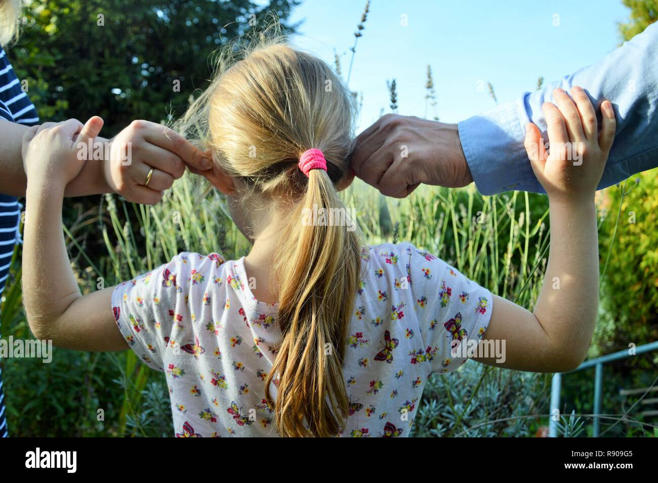 Little girl pulled by her ears by her parents. Educational lesson. Family ties - Stock Image