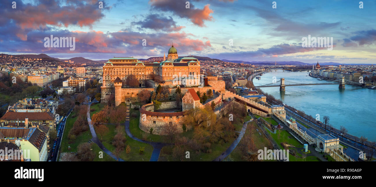 Budapest, Hungary - Golden sunrise at Buda Castle Royal Palace with Szechenyi Chain Bridge, Parliament and colorful clouds - Stock Image