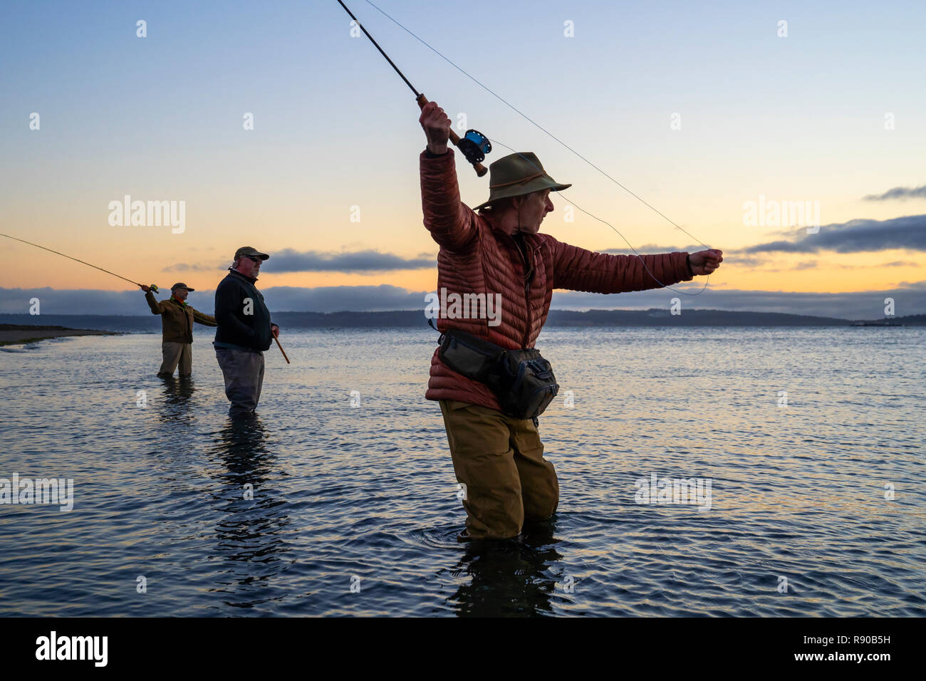 Two fly fishermen cast for searun coastal cutthroat trout and salmon with their guide standing between them on a salt water beach on a beach on the we Stock Photo