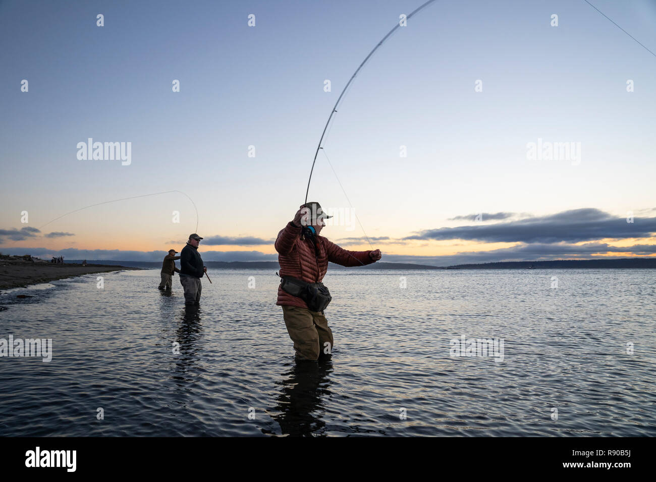 Two fly fishermen cast for searun coastal cutthroat trout and salmon with their guide standing between them on a salt water beach  on a beach on the w Stock Photo