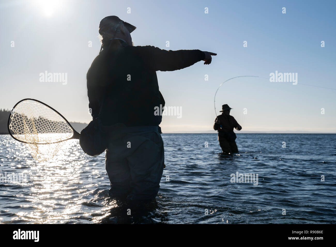 A guide advises his client while fly fishing in salt water