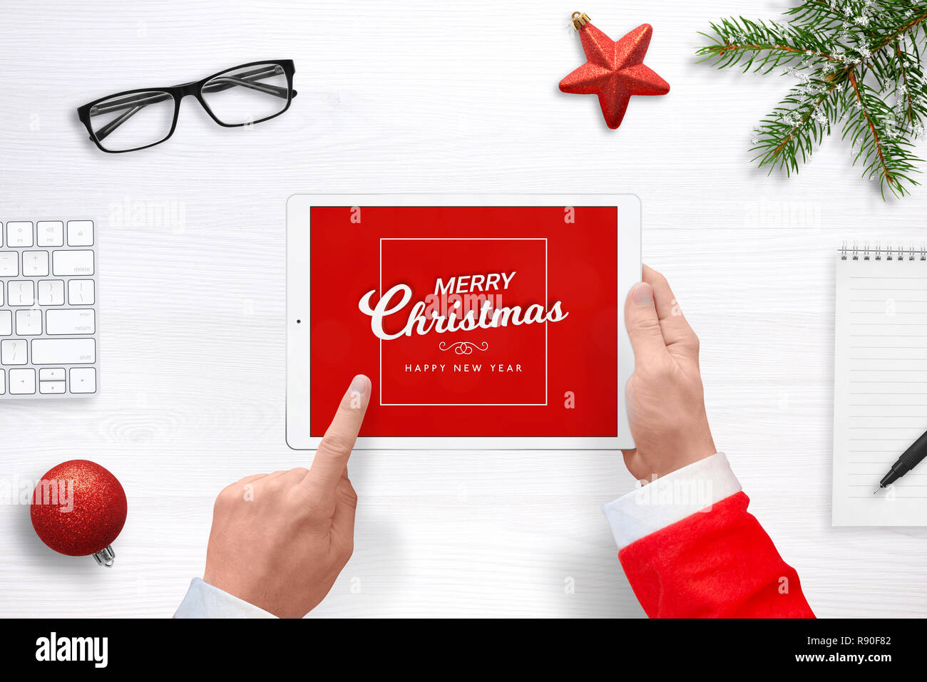 Santa work send greeting mail with tablet. Top view composition with Christmas decorations. - Stock Image