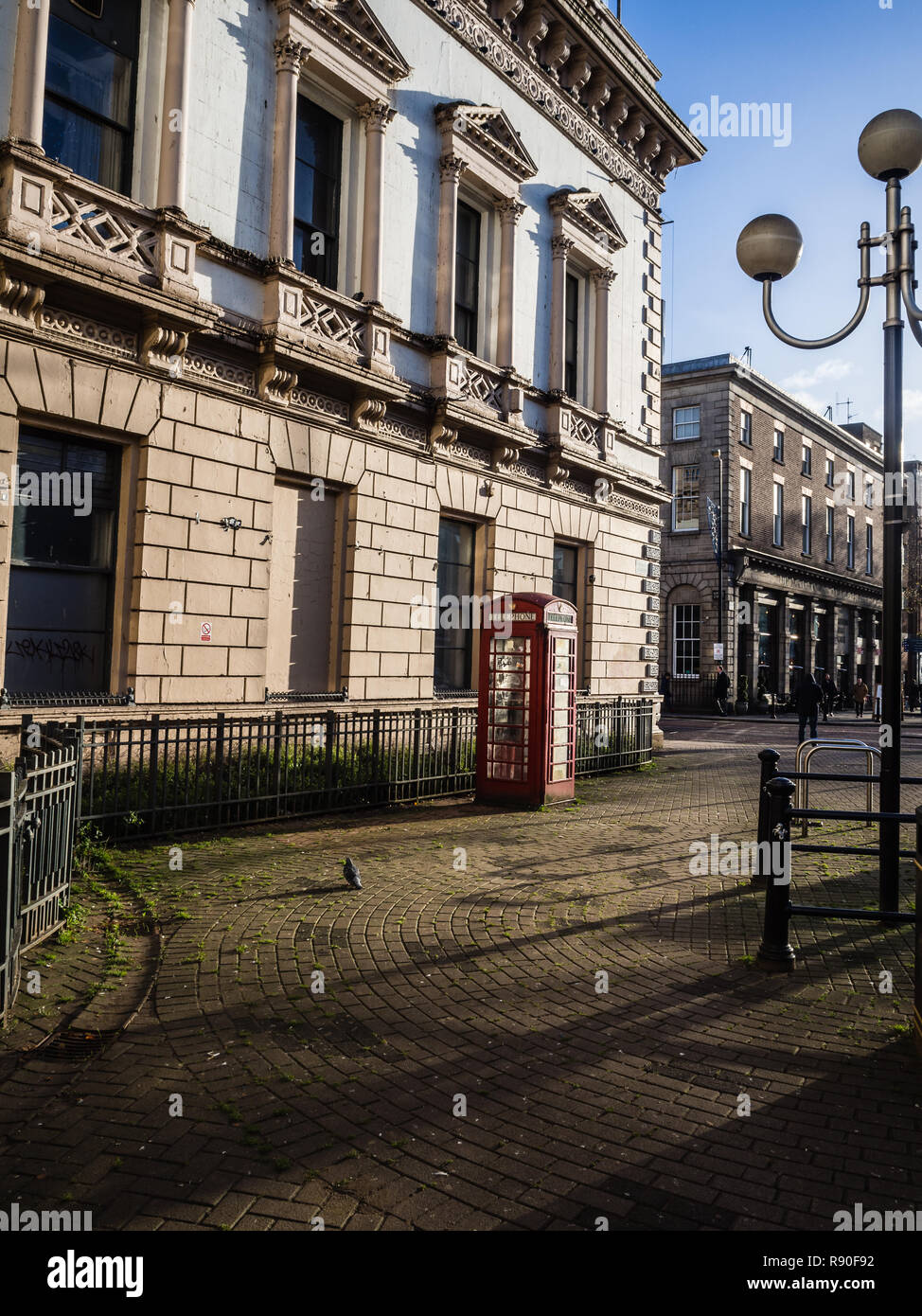 Delapidated historical building in Belfast with iconic red telephone box - Stock Image