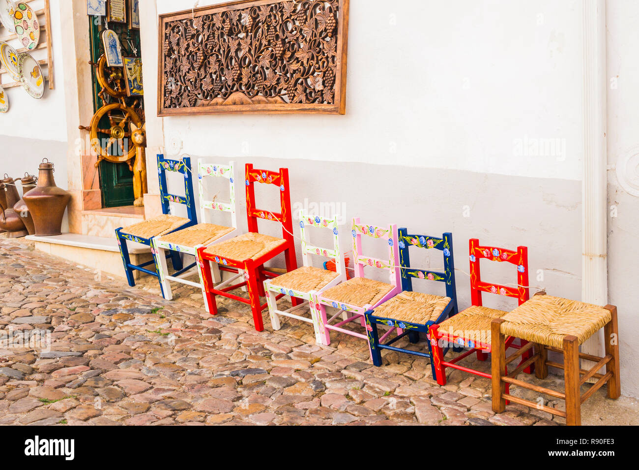 typical multicolored handmade chairs in front of a store selling local handicraft Stock Photo