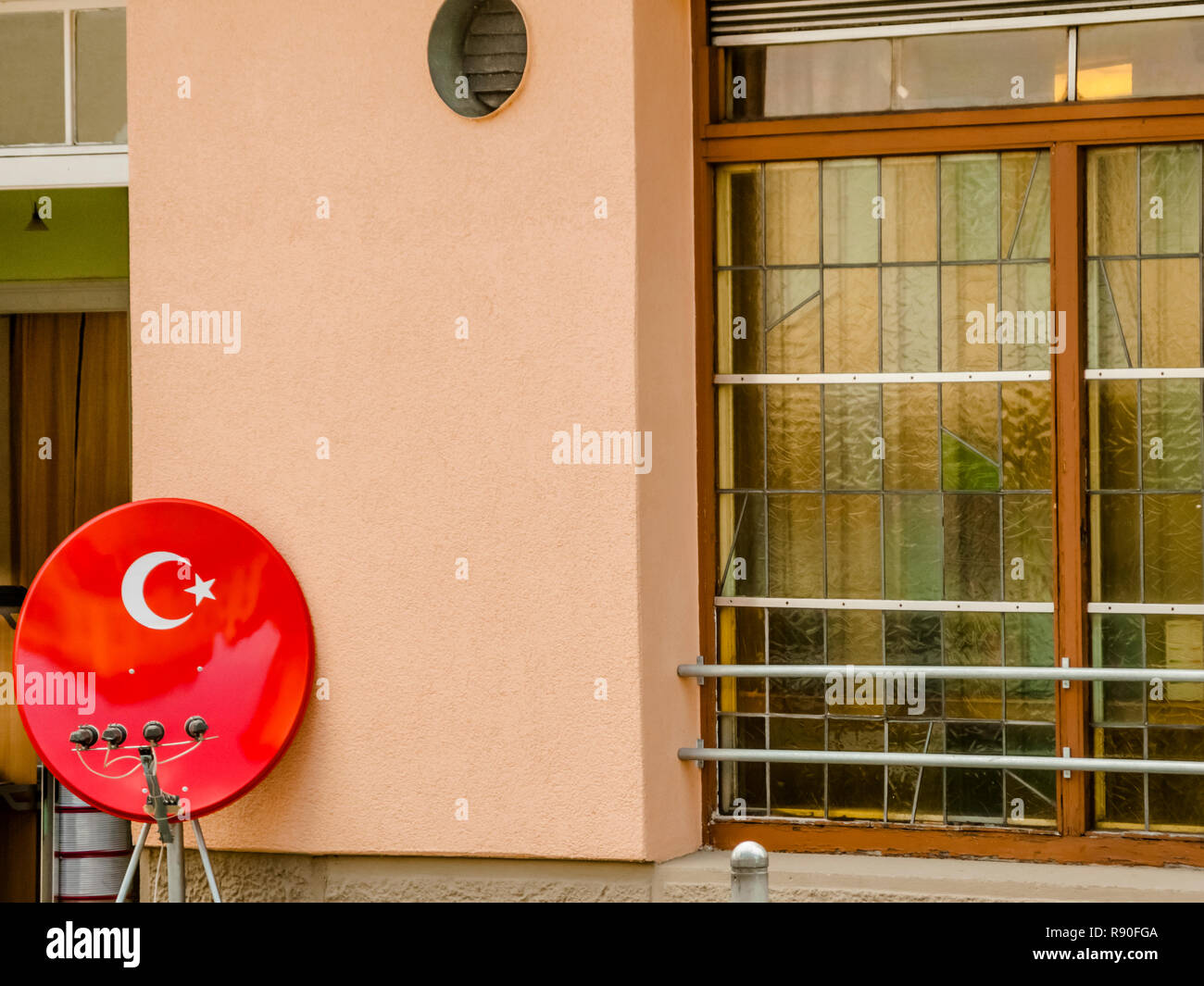 satellite receiver dish in the colors of the turkish national flag in front of a restaurant - Stock Image