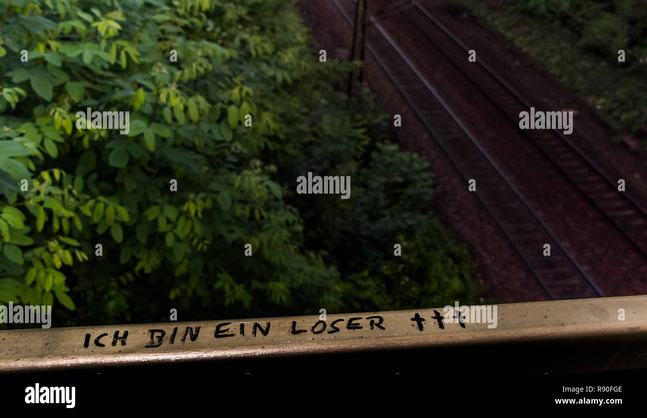 graffito on the parapet above a railway line, text: 'i am a loser' - Stock Image