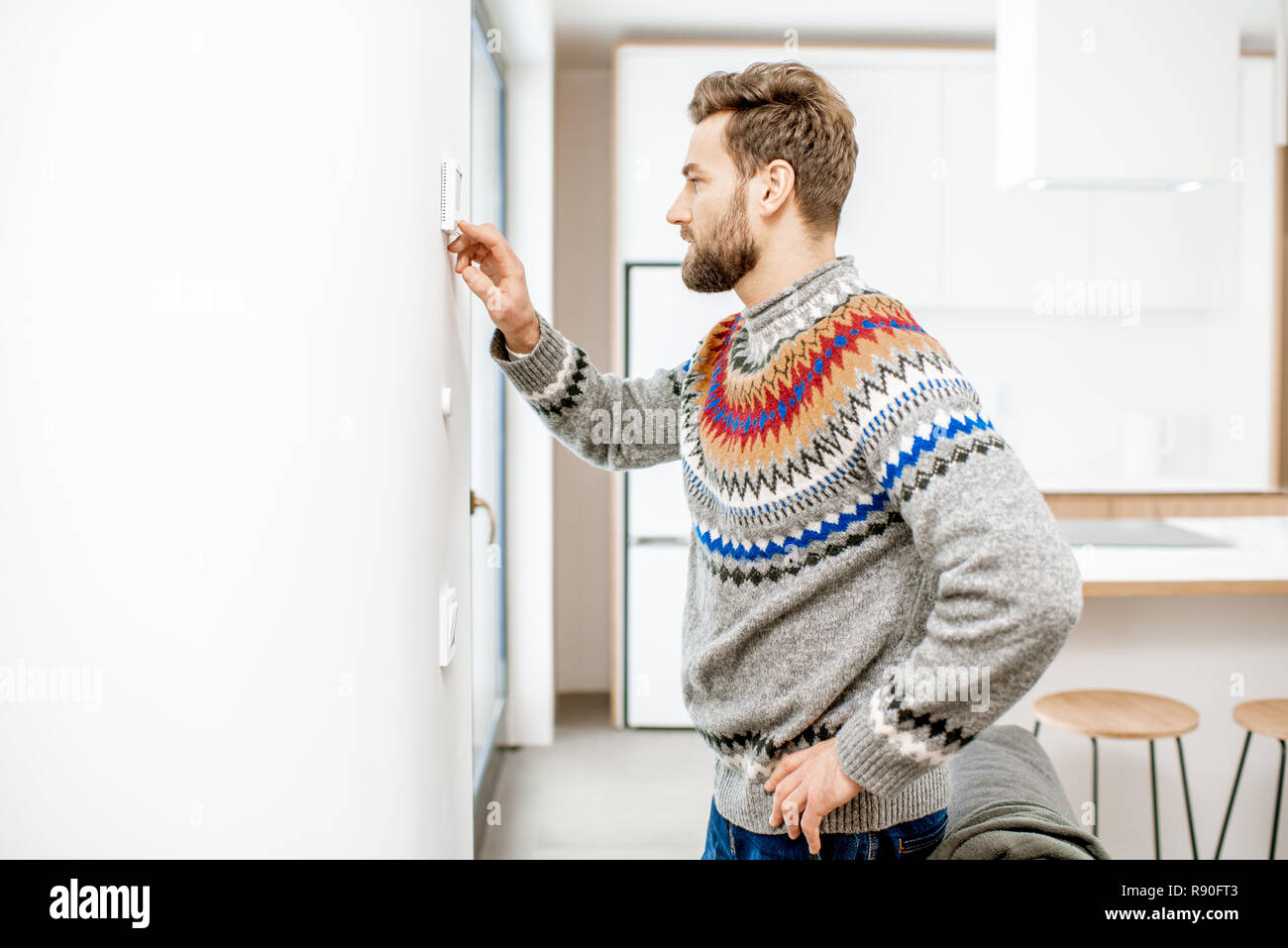 Man in sweater adjusting room temperature with electronic thermostat at home - Stock Image