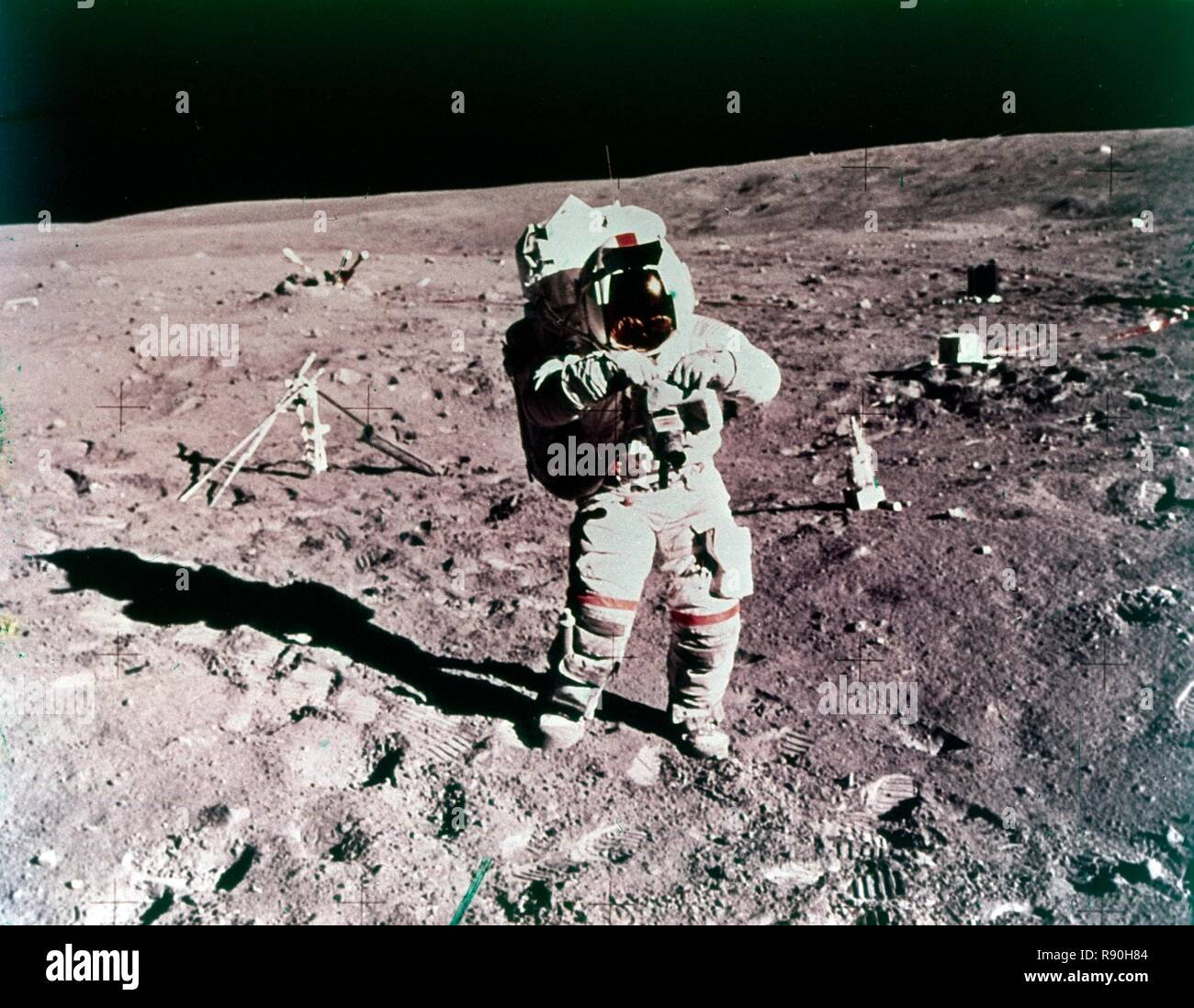 Astronaut John Young on the lunar surface, Apollo 16 mission, 21 April 1972. Commander John Young performing the first Apollo 16 Spacewalk at the Apollo Lunar Surface Experiments Package (ALSEP) deployment site, Descartes landing site. The lunar surface drill is just behind and to the right, rack and bore stems (left), with the three-sensor Lunar Surface Magnetometer beyond. The dark object in the right background is the Radioisotope Thermoelectric Generator (RTG). Between the RTG and the drill is the Heat Flow Experiment. - Stock Image