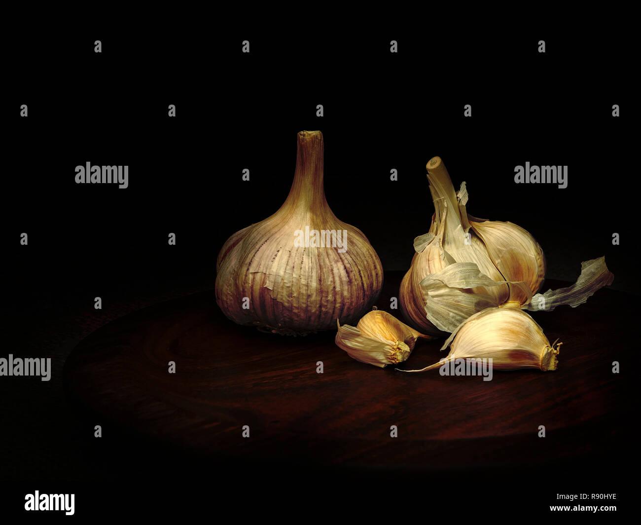 Chiaroscuro garlic on wooden plate. Still life, light painting. - Stock Image