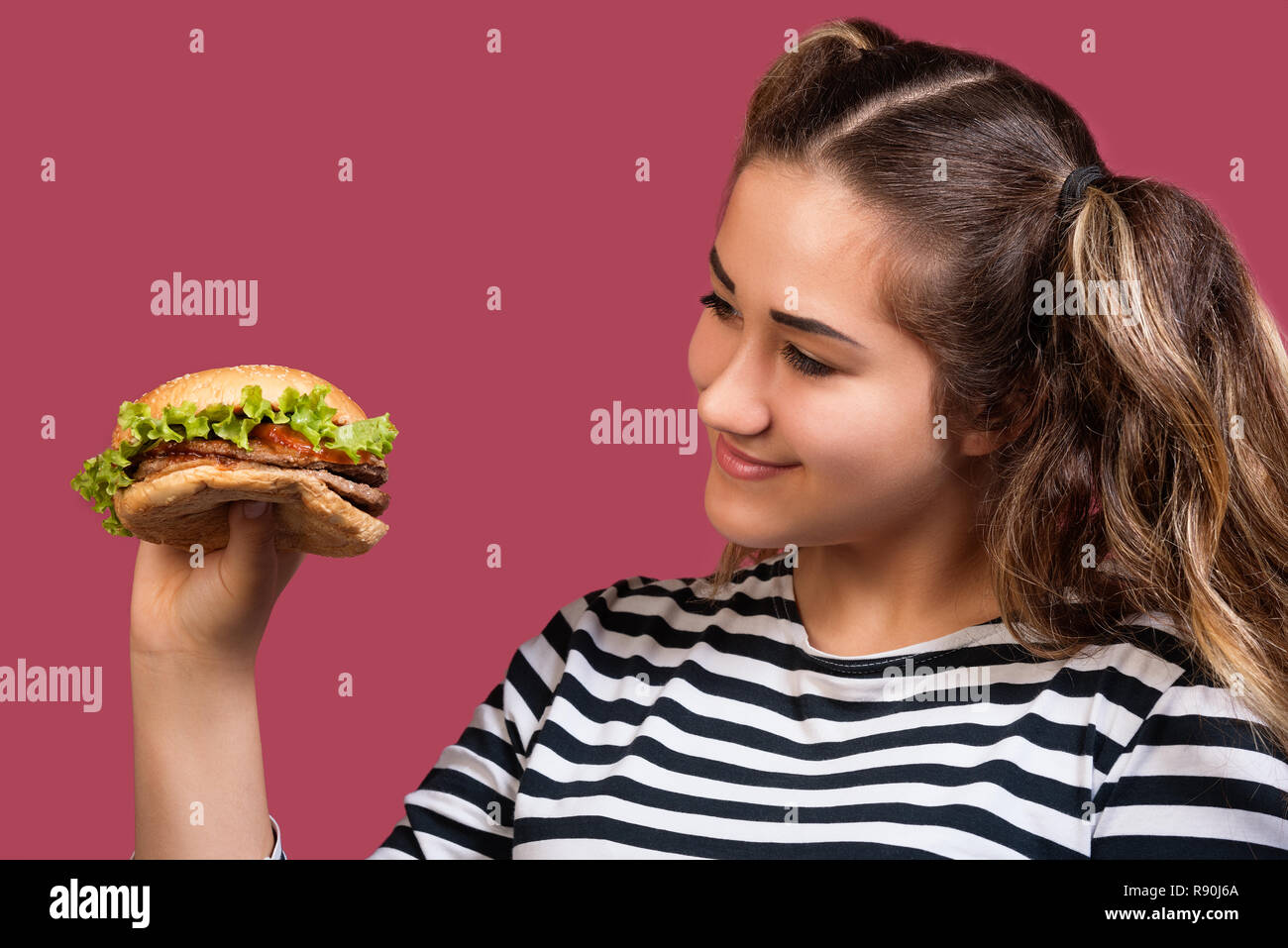Close up portrait of cool girl with ponytails looking at hamburger over colorful pink background - Stock Image