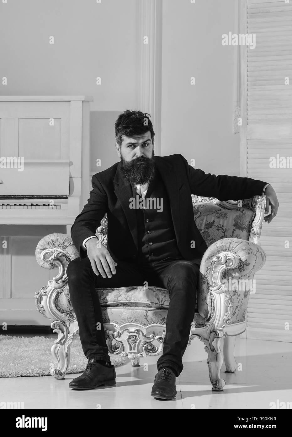 Wealth and richness concept. Man with beard and mustache wearing classic suit, stylish fashionable outfit. Macho attractive and elegant on serious, thoughtful face sitting on old fashioned armchair. - Stock Image