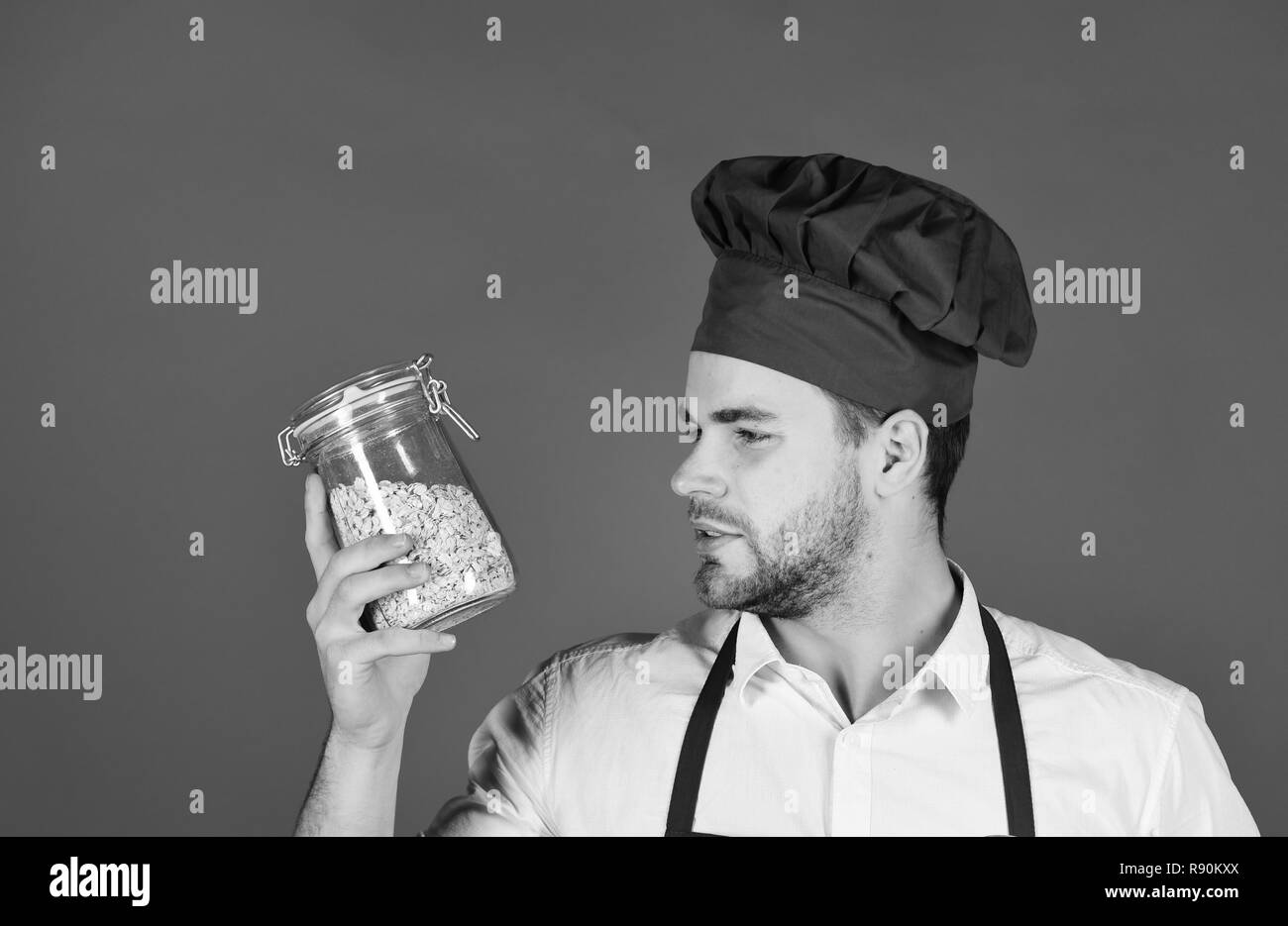 Chef in burgundy uniform holds jar with groats. Breakfast and healthy food concept. Cook with thoughtful face and jar. Man with beard holds glass jar with porridge on red background. - Stock Image