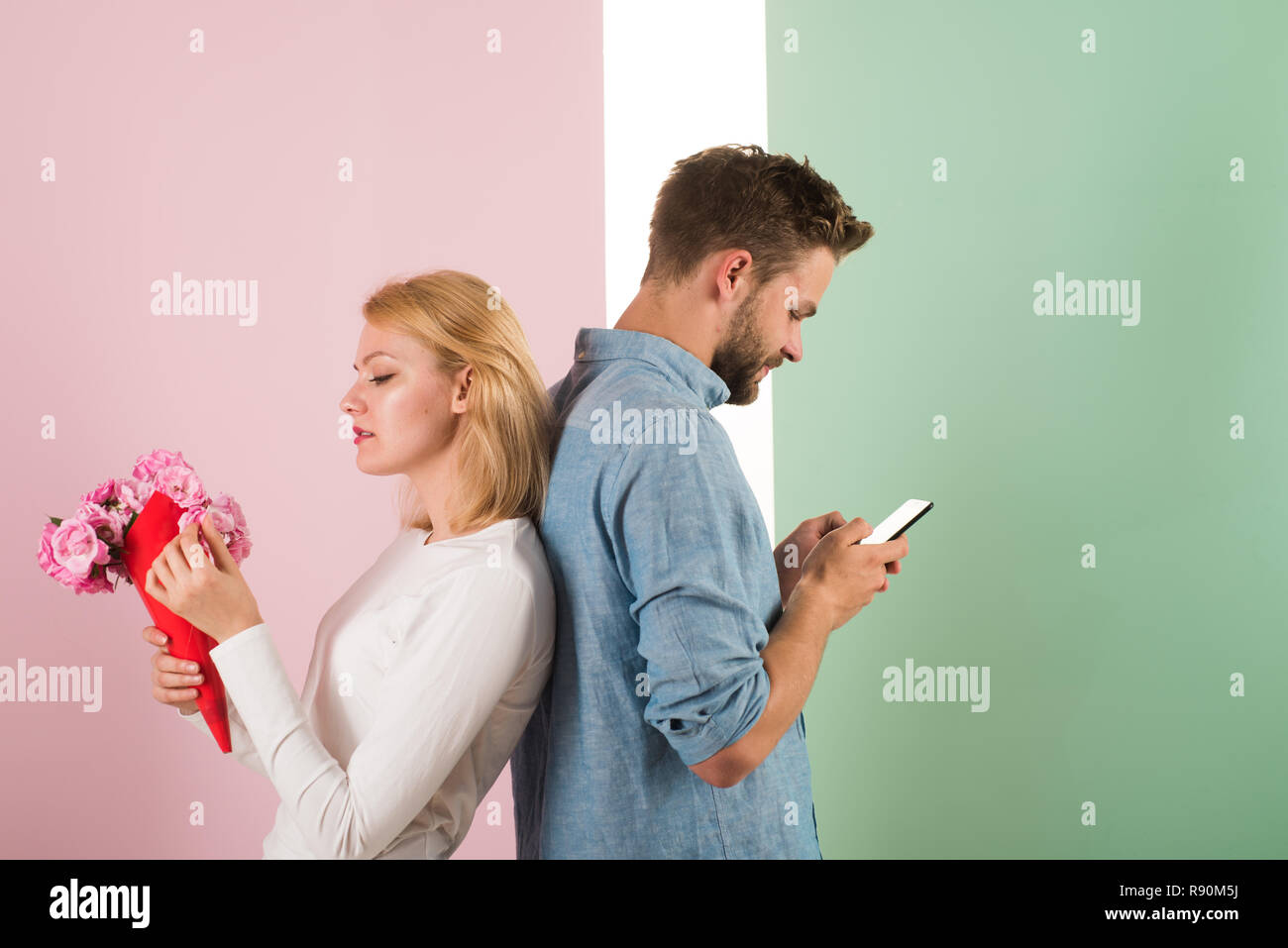 Guy with phone and girl with bouquet flowers, pastel background. Cheating concept. Man hold smartphone texting lover while stands back to back wife. Woman with flowers blind about unfaithful husband. - Stock Image