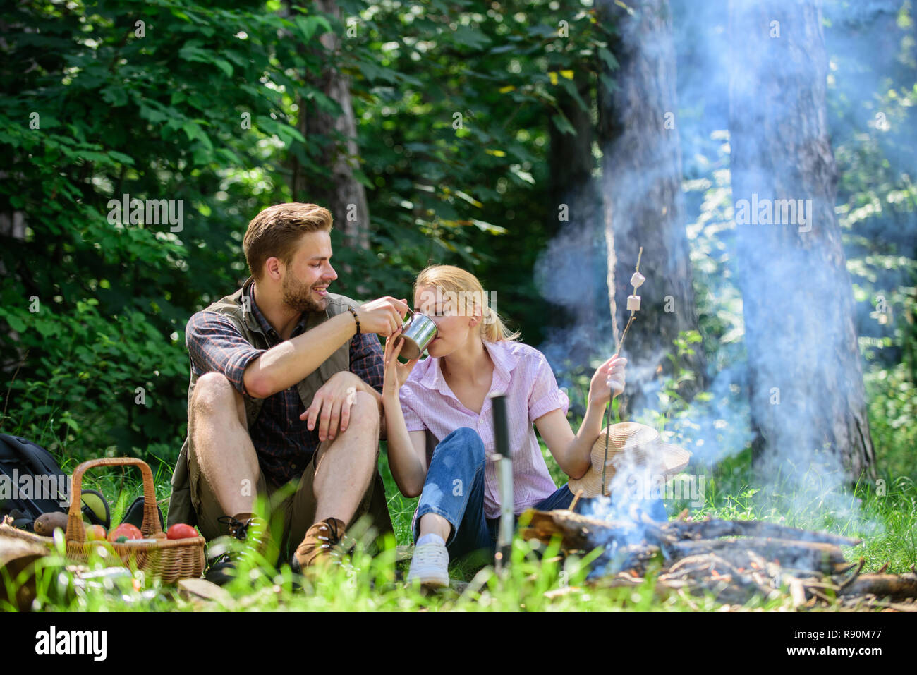 Weekend picnic. Food for hike and camping. Couple sit near bonfire eat snacks and drink. Couple in love camping forest hike. Hike snacks and beverages. Couple take break to eat nature background. - Stock Image