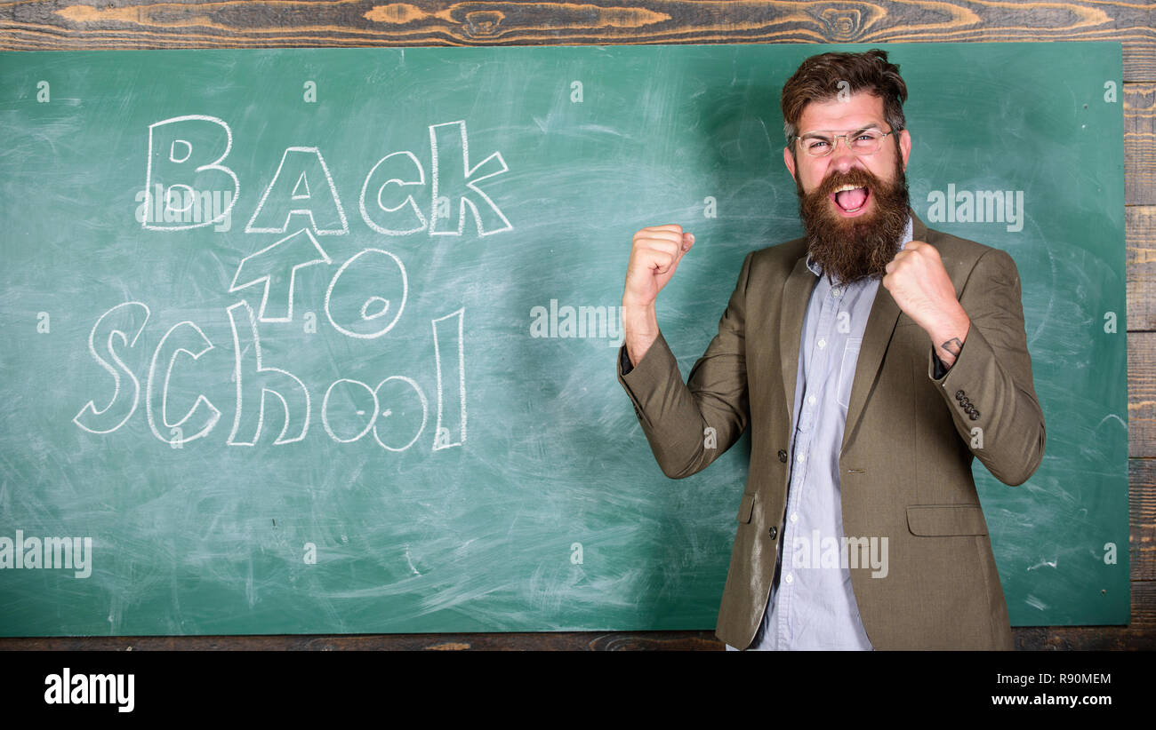 Invitation to celebrate knowledge day. Teacher begin first lesson after holidays. Invite to school. Teacher or educator welcomes students while stands near chalkboard with inscription back to school. - Stock Image